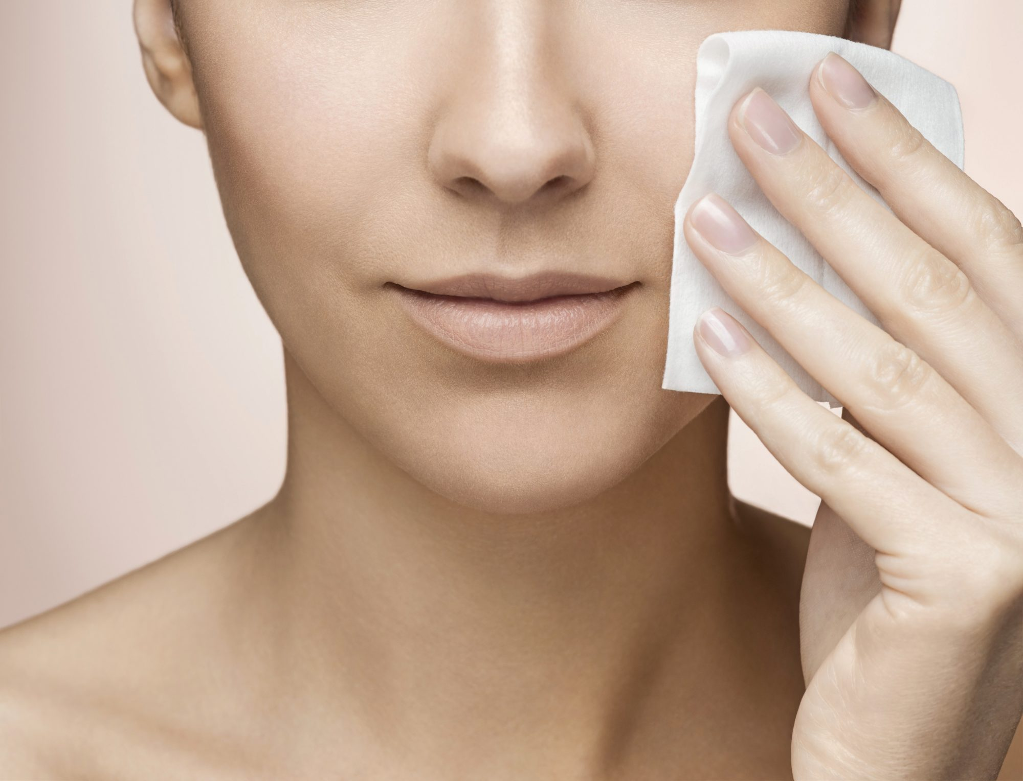 Young woman wiping face with tissue