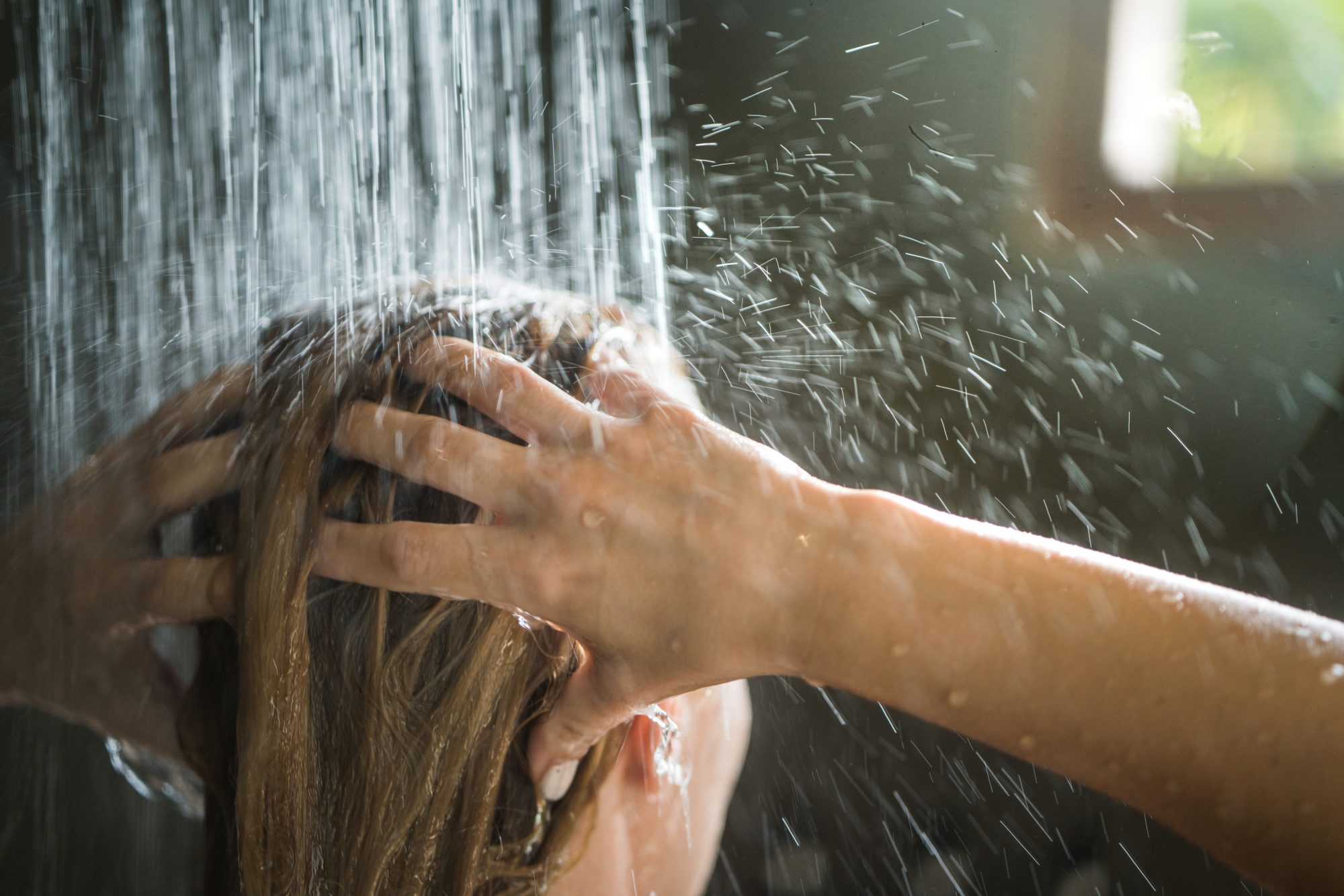 Close up of unrecognizable woman washing her hair under the shower.