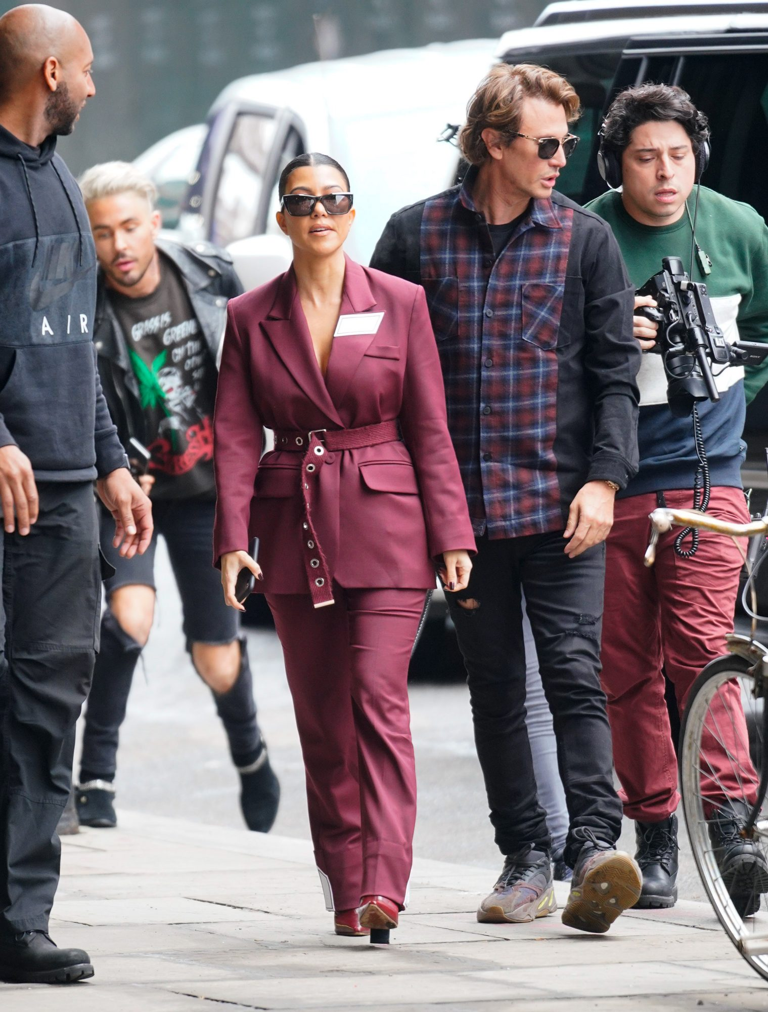 Kourtney Kardashian Wearing a Burgundy Suit with Matching Boots
