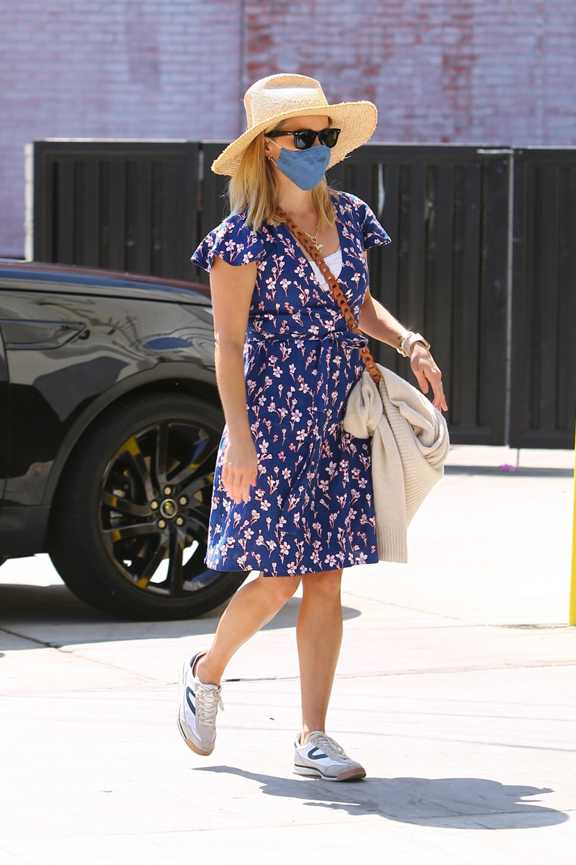 Reese Witherspoon wearing a straw hat and a floral dress.