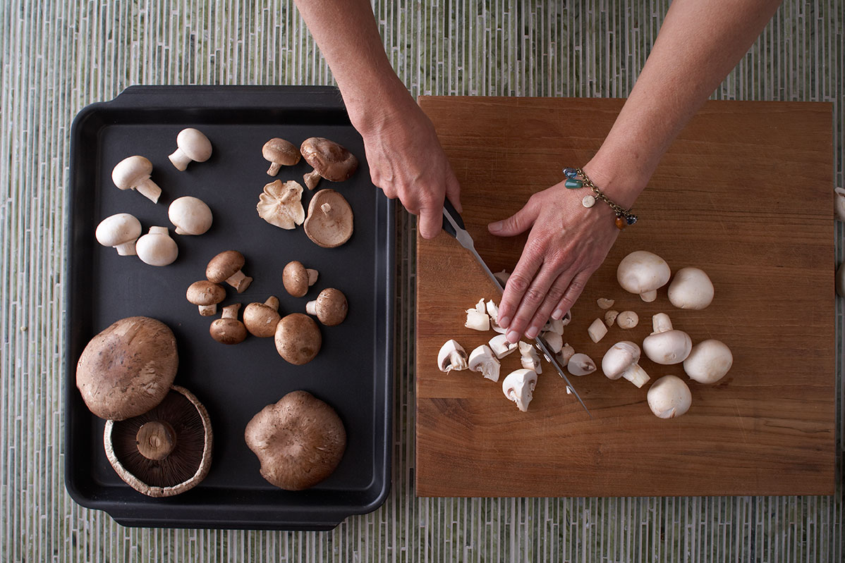 person cutting mushroom son cutting board next to baking sheet with different types of mushrooms
