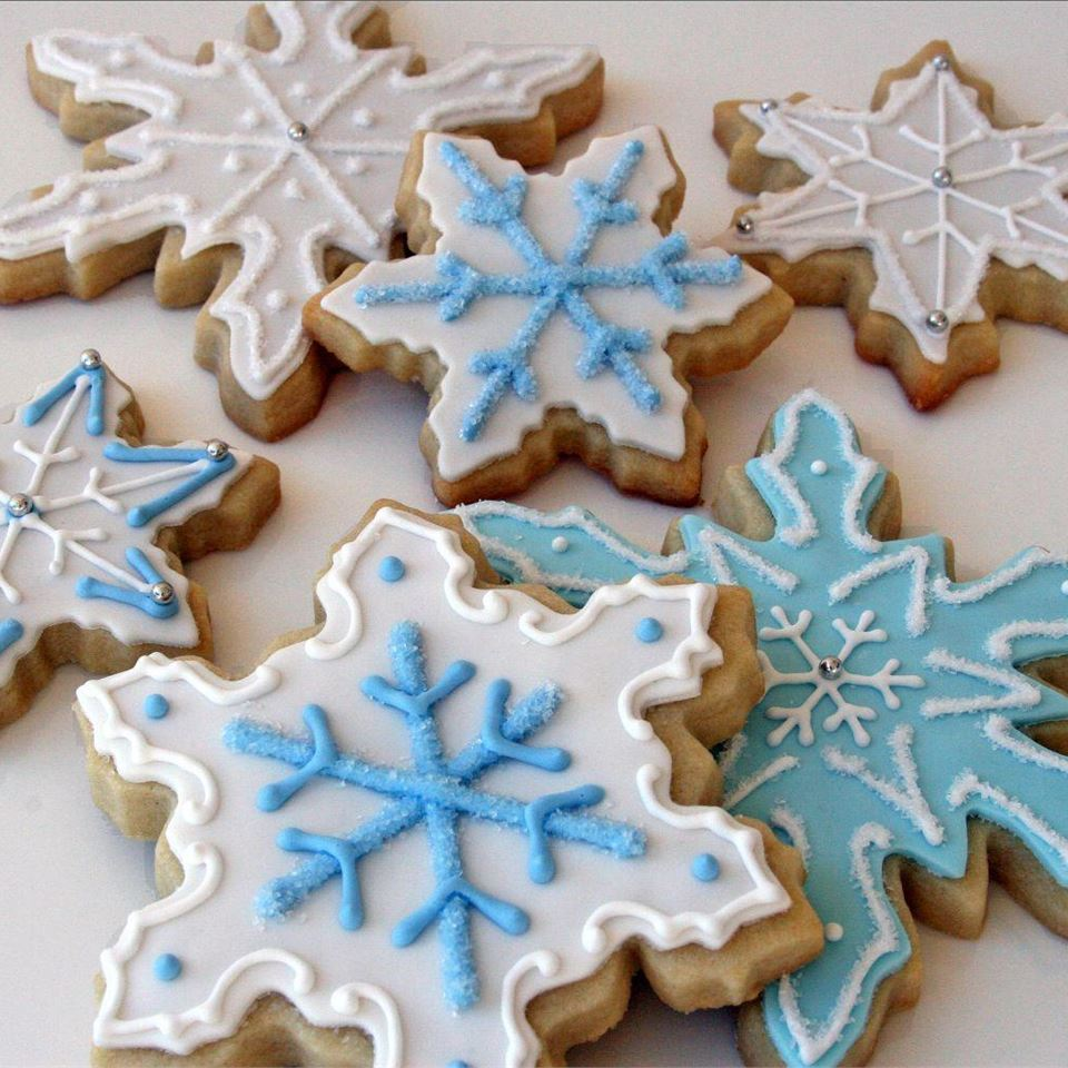 Sugar cookies decorated to look like snowflakes with white icing and two shades of pale blue icing