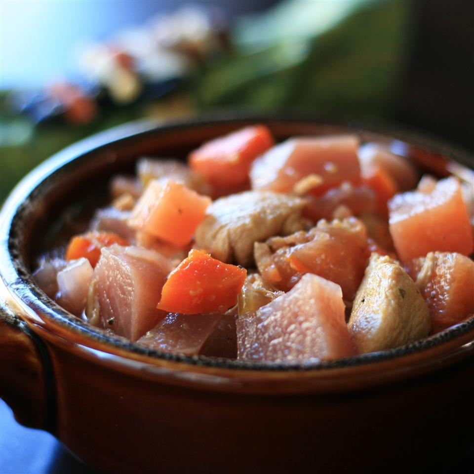 a stew of diced chicken, potatoes, carrots, onion, and rutabaga in a brown clay bowl
