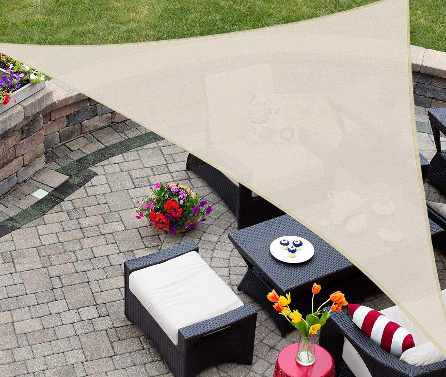 tan triangle shaped sun shade from AsterOutdoor over a patio set in a yard