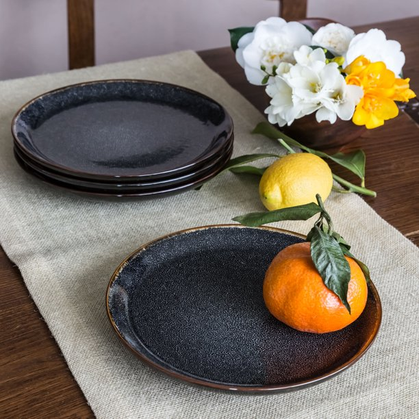 set of four black salad plates on a table