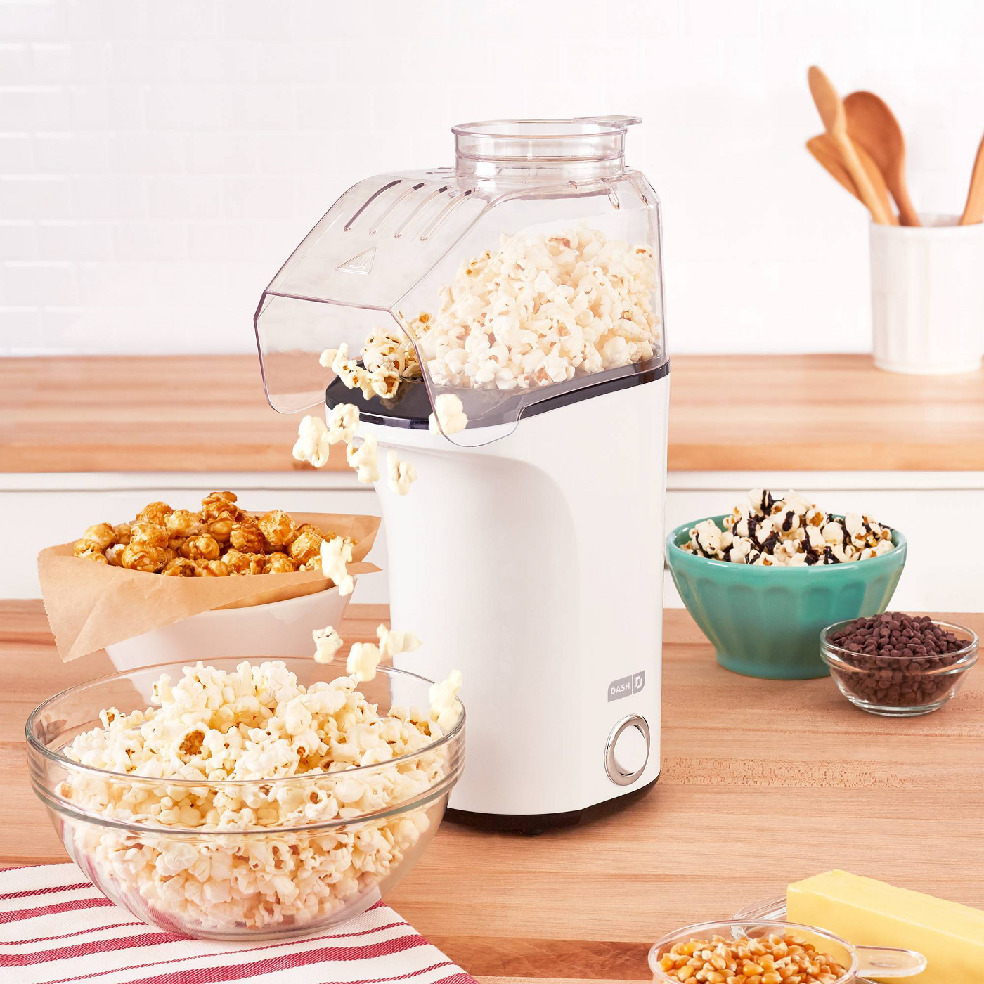 White dash popcorn maker pouring popcorn into a bowl