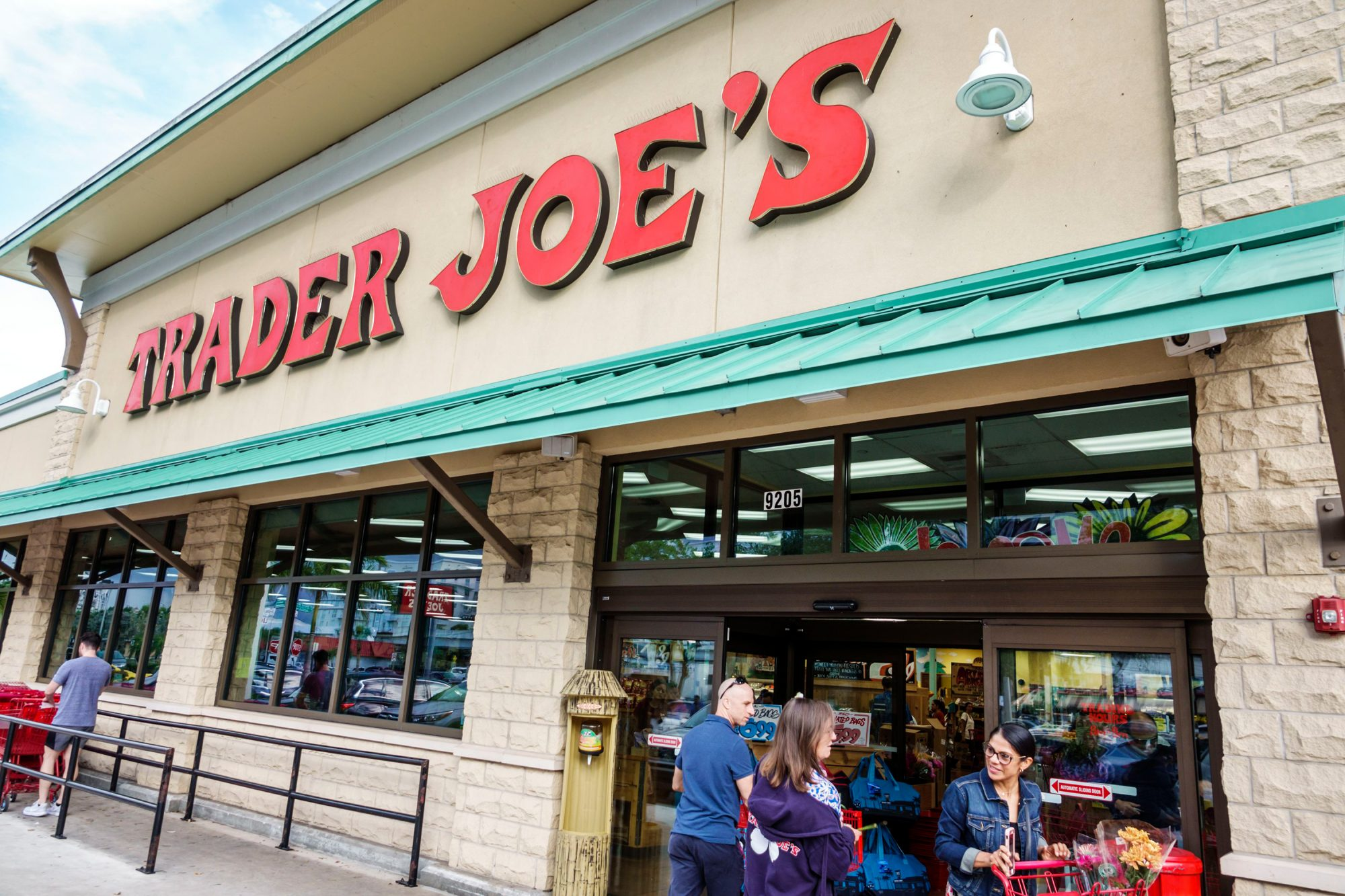 people standing in front of a trader joe's store