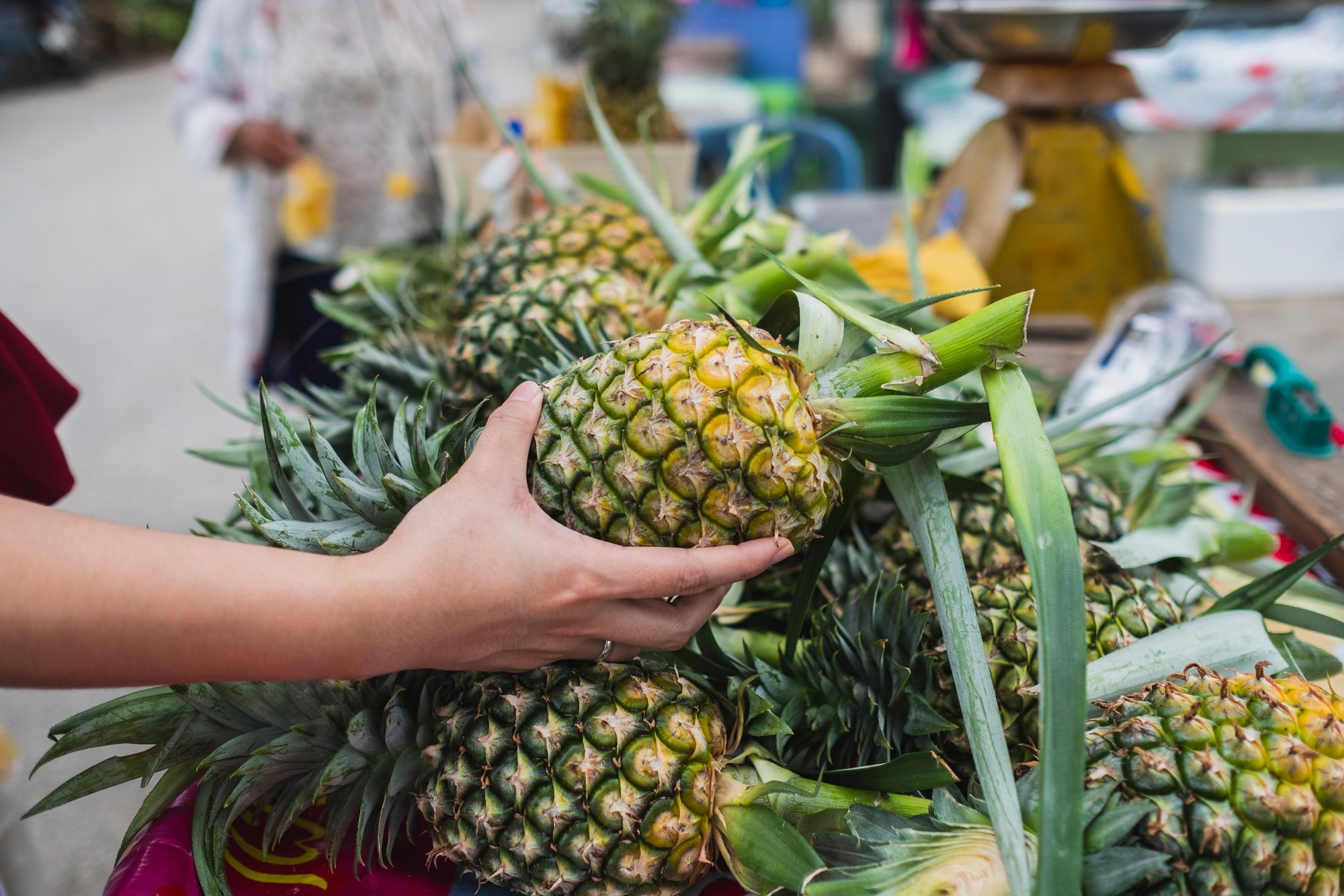Close-Up Of Woman Buying Pineapple At Market Stall
