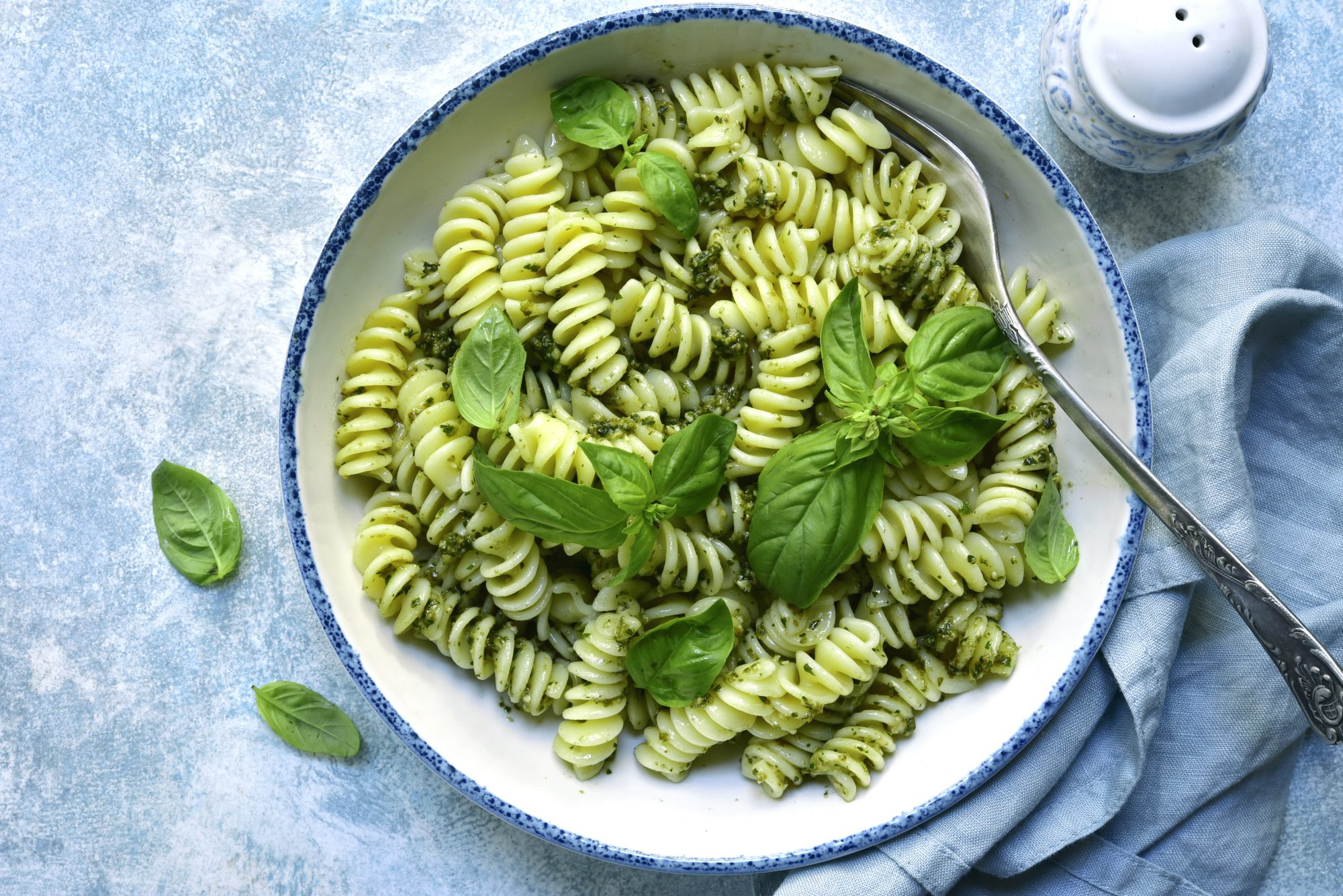 Fusilli pasta with pesto sauce in a white bowl on a light blue slate, stone or concrete background. Top view with copy space.