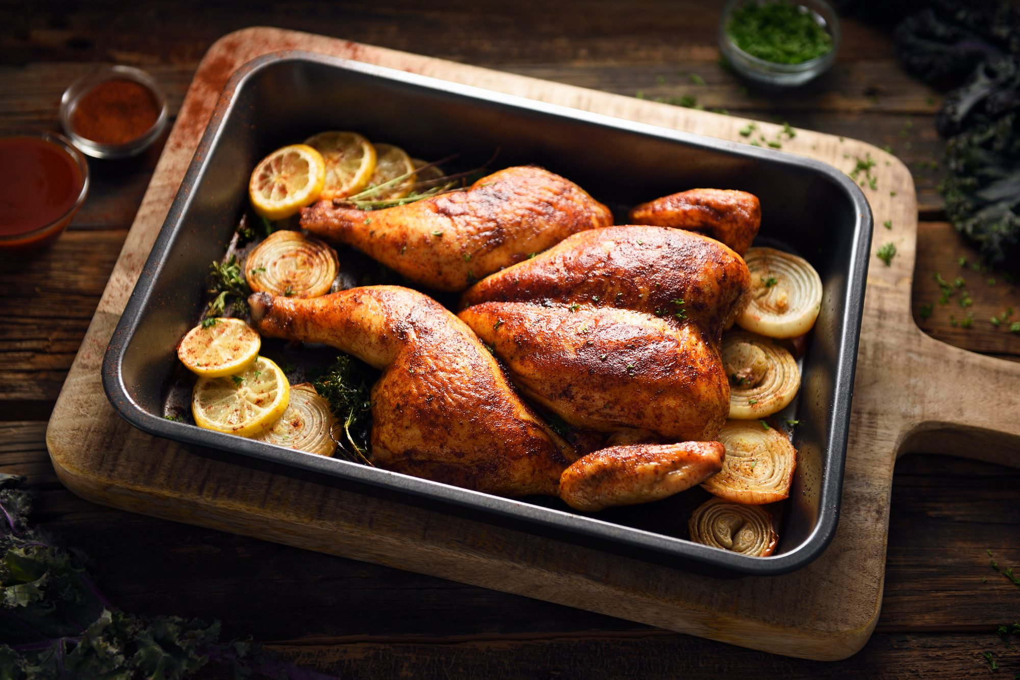 Butterflied roast chicken on a pan with lemons