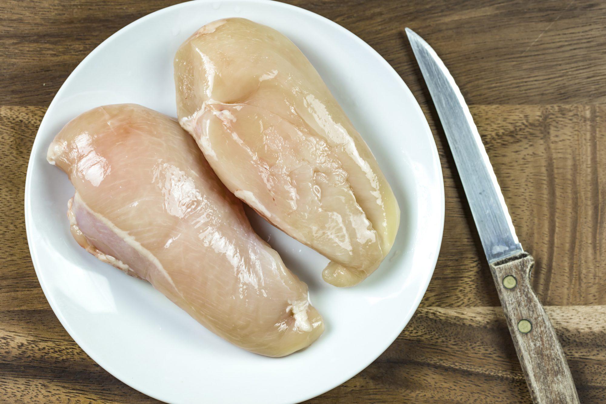 Raw chicken breast on white plate