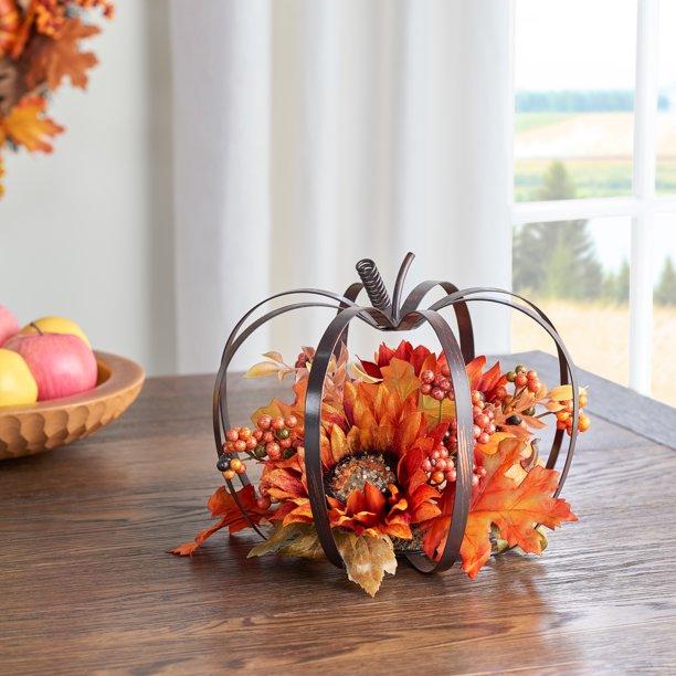 bronze pumpkin decoration with faux floral arrangement inside