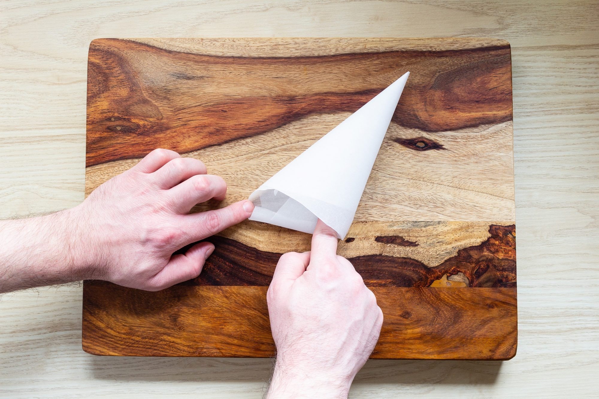 double folding the edge of a parchment paper piping bag