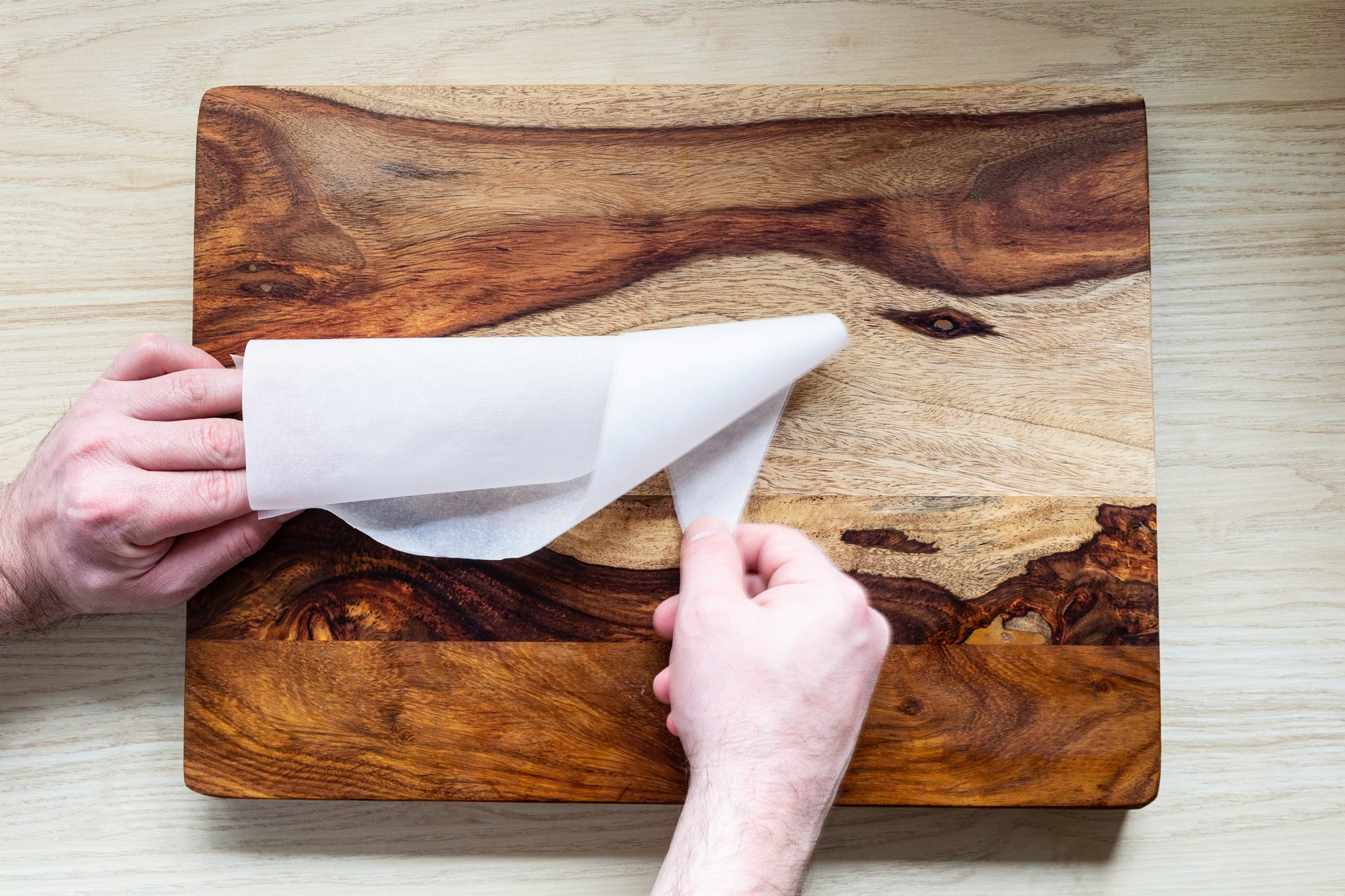 folding a parchment paper triangle to make a piping cone