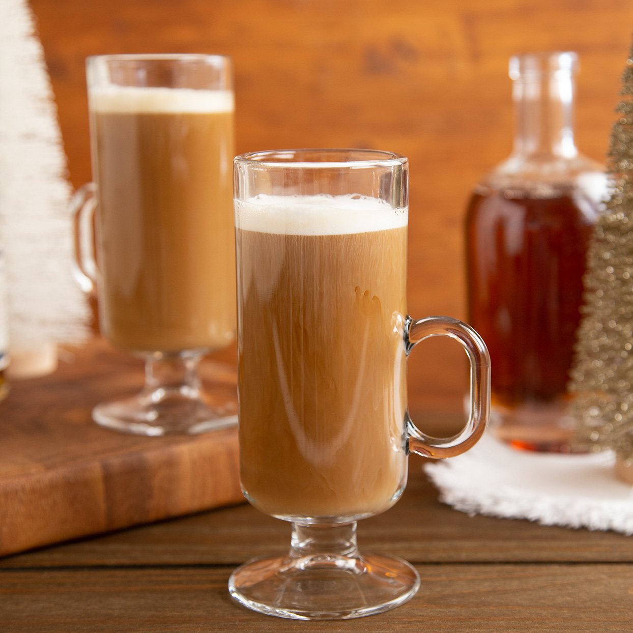 two clear mugs of spiked coffee with milk