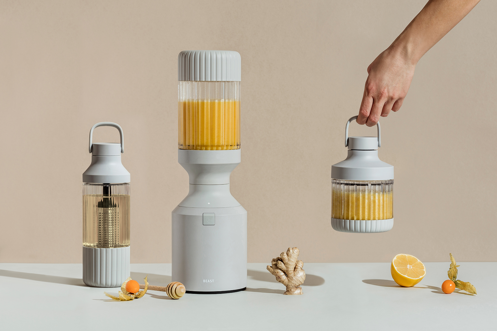 Beast Health - The Beast Blender with a hand holding a finished smoothie and other fruits and vegetables on a table