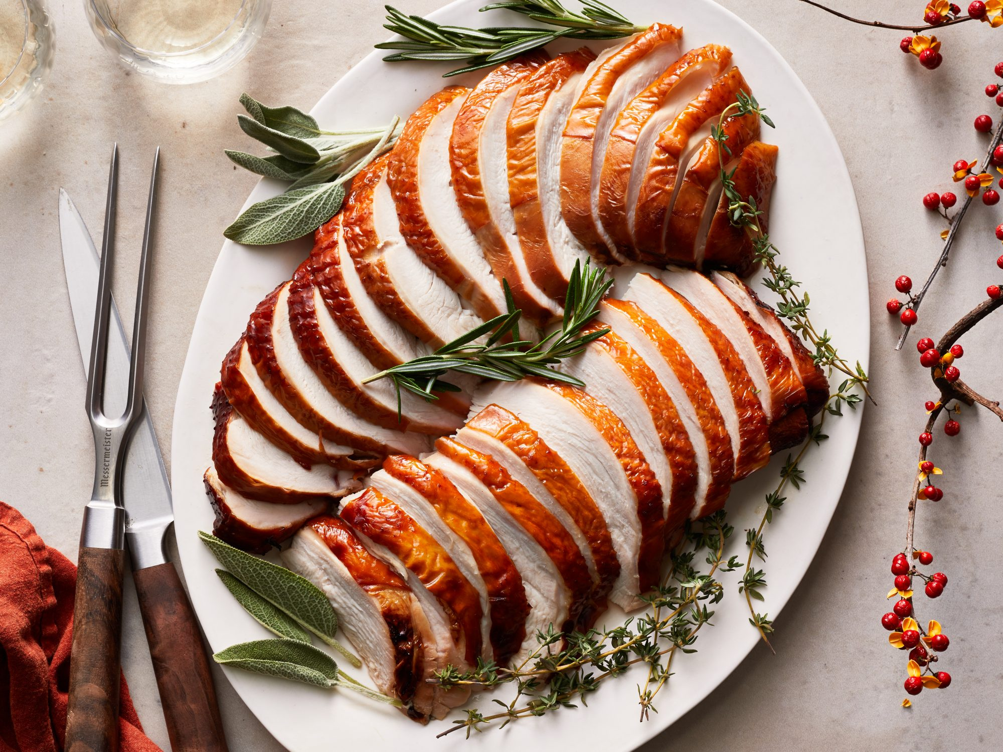 Sliced, smoked turkey breast arranged on a white serving platter with herbs.