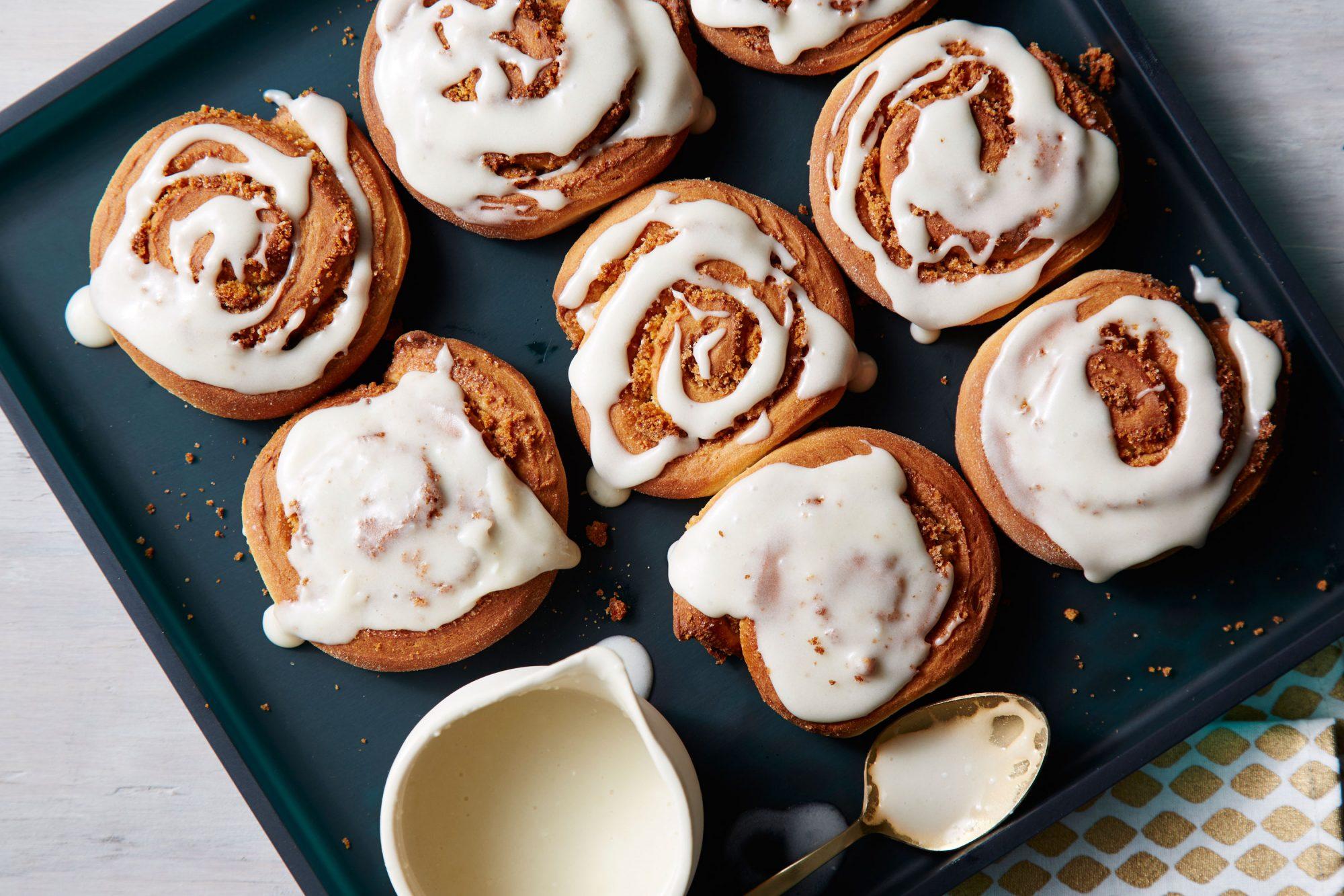 Freshly glazed cinnamon rolls on a serving platter.