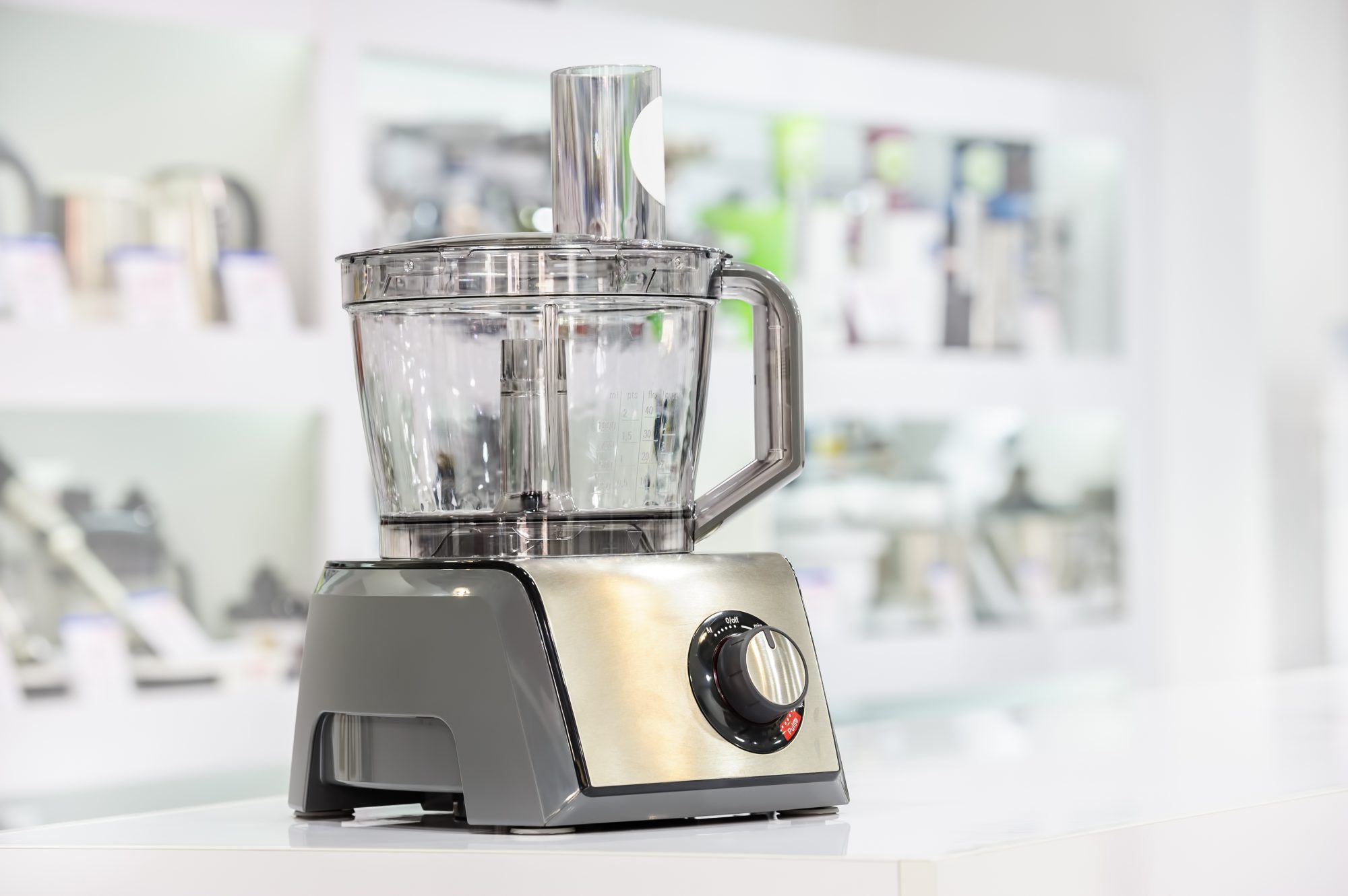 single electric food processor at retail store shelf, defocused background