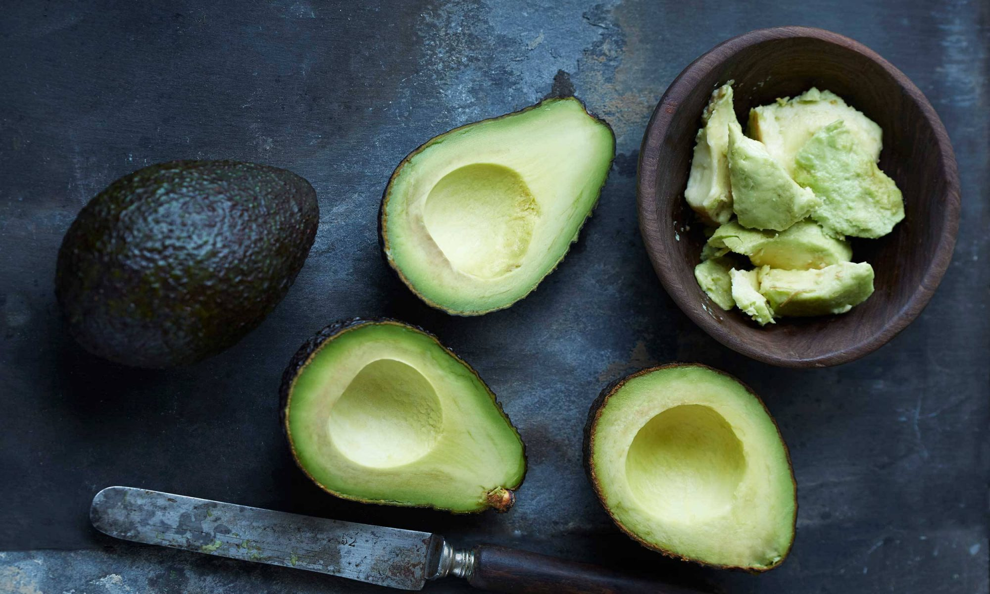 Whole, cut, and mashed avocado on a dark background