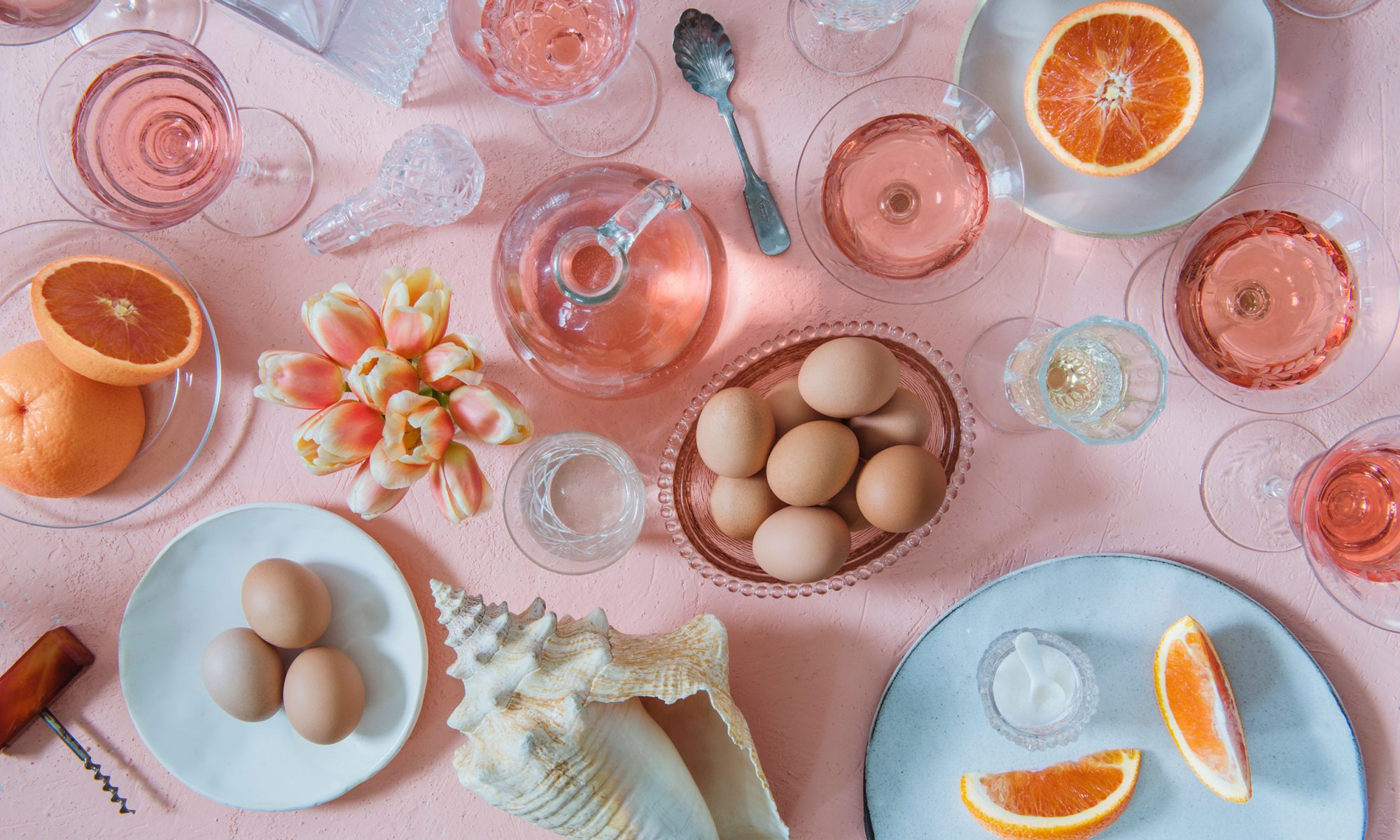 All-pink breakfast spread with eggs, grapefruit, rosé and a conch shell
