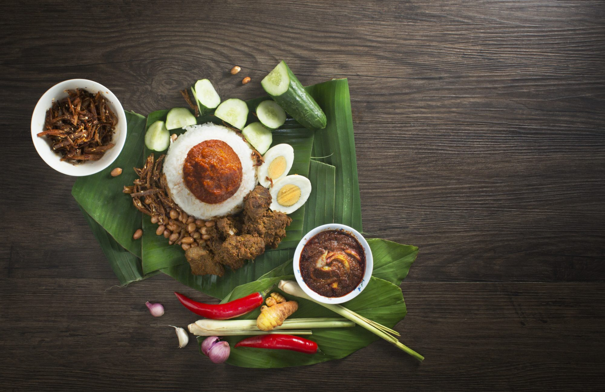 """Malaysia traditional food """"Nasi lemak"""" and ingredients on rustic wooden table top."""