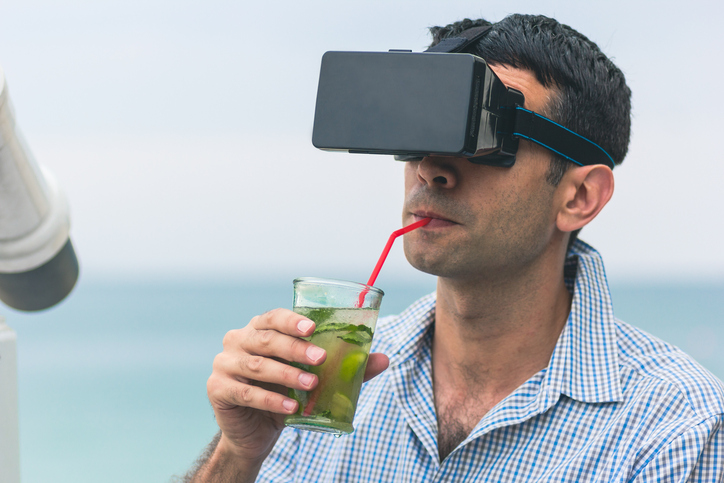 Young Man Using Virtual Reality Simulator While Drinking Cocktail Against Sea