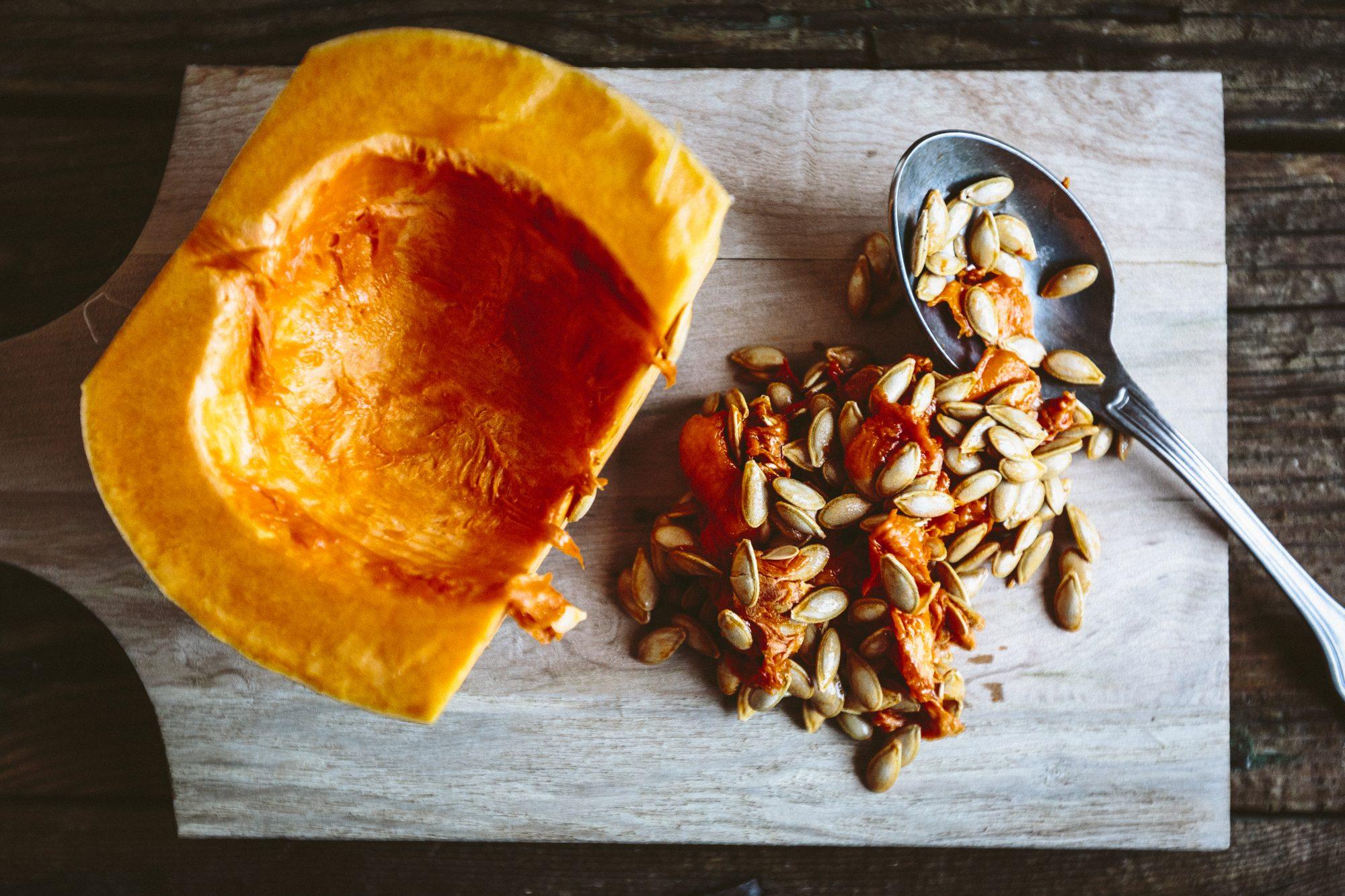 Cut pumpkin with pumpkin seeds and spoon.