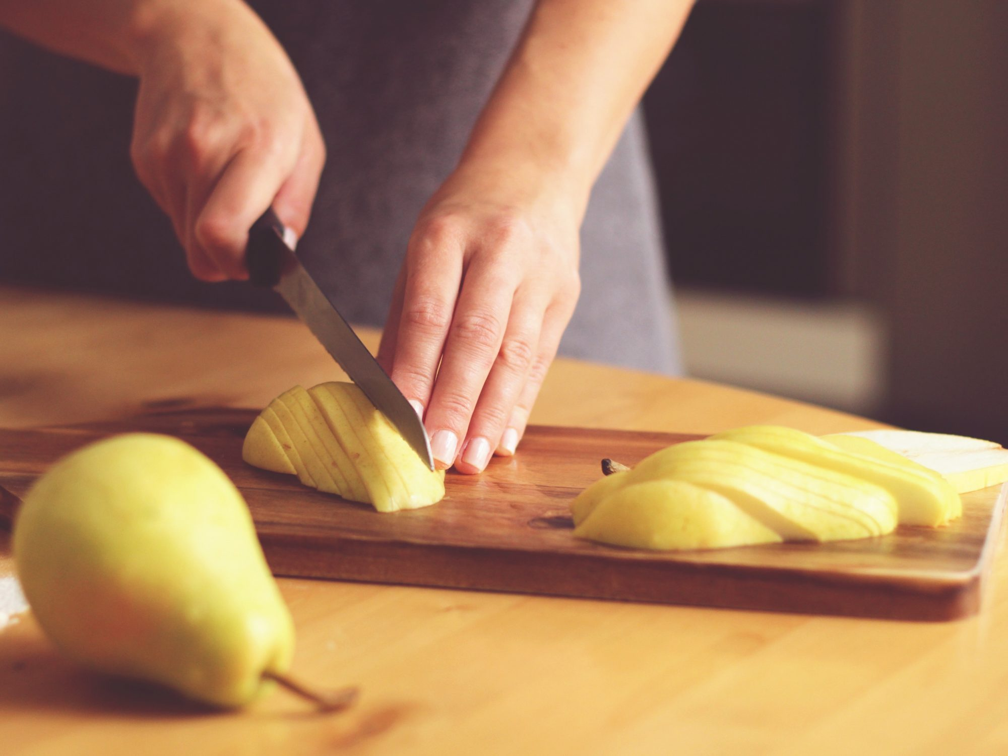 Woman Chopping Pear With Knife On Cutting Board