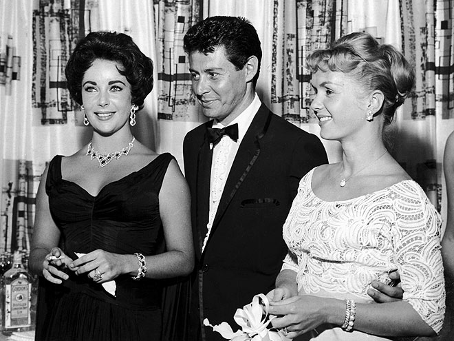 1958: American singer Eddie Fisher, wearing a tuxedo, stands with arm around his wife, American actor Debbie Reynolds (R) and smiles while looking at British-born actor Elizabeth Taylor, smoking a cigarette, Las Vegas, Nevada.