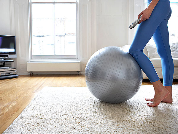 Woman with exercise ball in front of TV