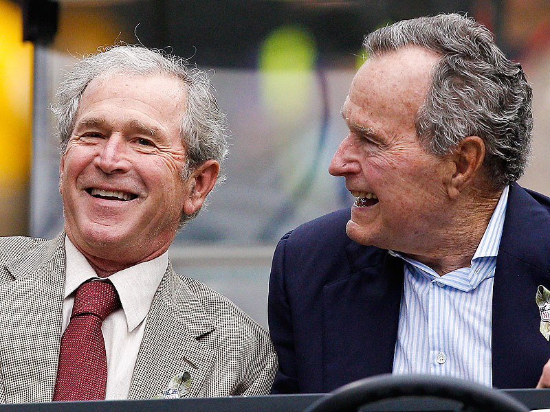 President George W. Bush, left, and President George H.W. Bush at Reliant Stadium before the Oakland Raiders play the Houston Texans on November 17, 2013 in Houston, Texas.