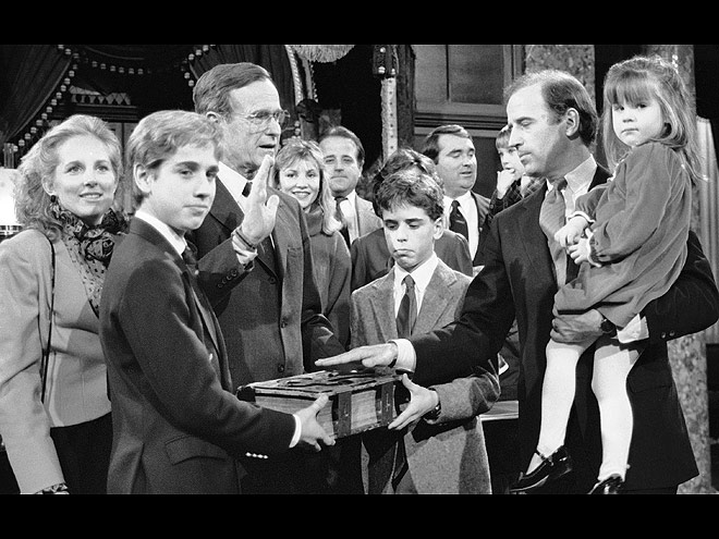 Jan. 3, 1985, Sen. Joe Biden (D-Del.) holds his daughter, Ashley, while taking a re-enacted oath of office from Vice President George Bush during a ceremony on Capitol Hill in Washington as his sons Beau, foreground, and Hunter hold the bible.
