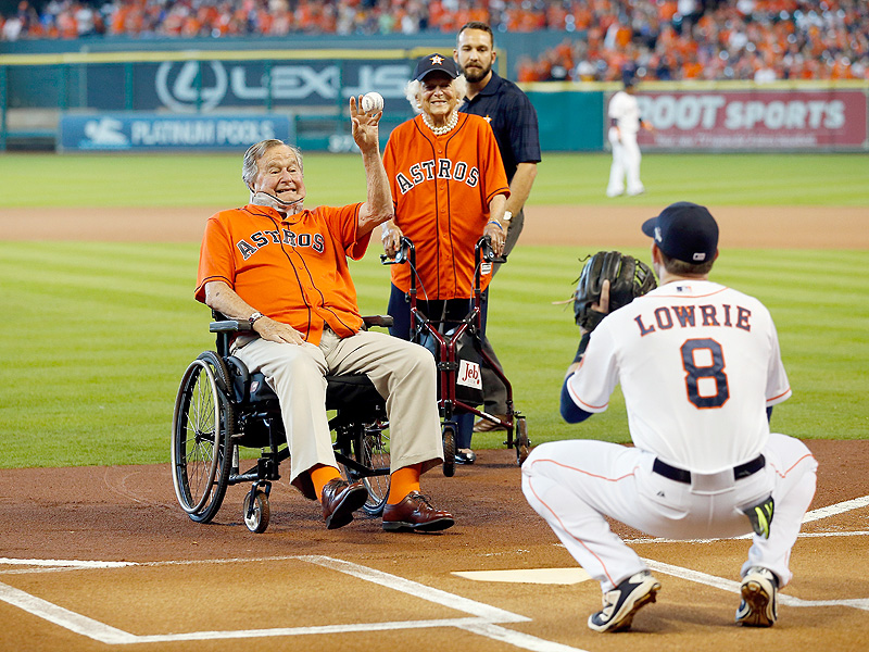 President George H.W. Bush throws out the ceremonial first pitch to Jed Lowrie #8 of the Houston Astros as former First Lady Barbara Bush looks on