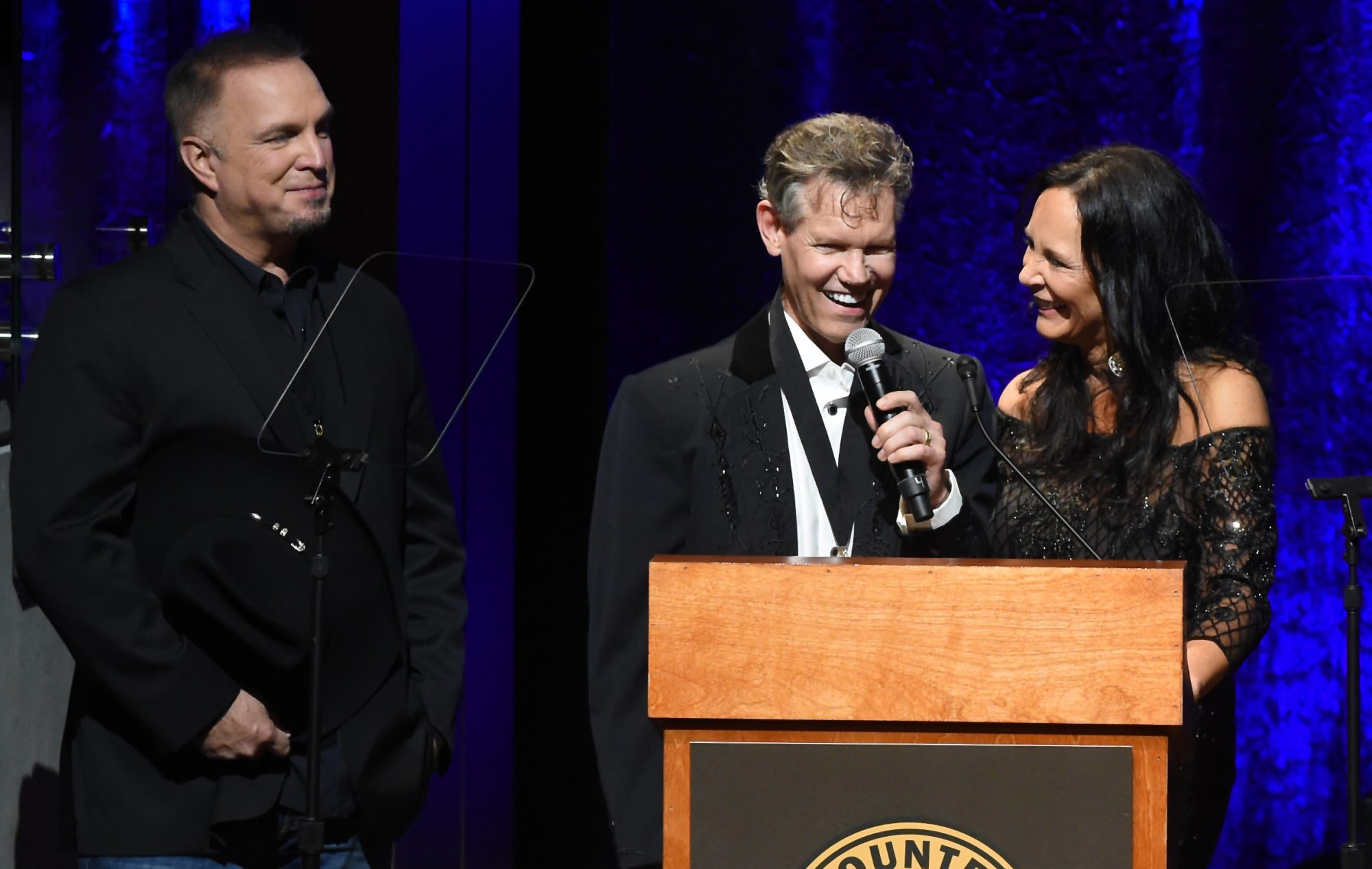 NASHVILLE, TN - OCTOBER 16:  Randy Travis sings 'Amazing Grace' with wife Mary Davis (R) and Garth Brooks (L) during the 2016 Medallion Ceremony at Country Music Hall of Fame and Museum on October 16, 2016 in Nashville, Tennessee.  (Photo by Rick Diamond/Getty Images for Country Music Hall of Fame & Museum)
