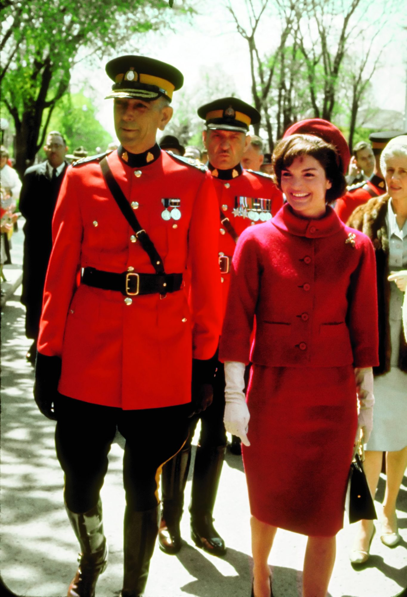 OTTAWA, CANADA - MAY 01: First Lady Jacqueline Kennedy (R) wearing a red wool suit by designer Oleg Cassini with a matching beret while standing with Royal Canadian Mounted Police Commissioner Clifford Harvison, during a state visit to Canada. The suit w