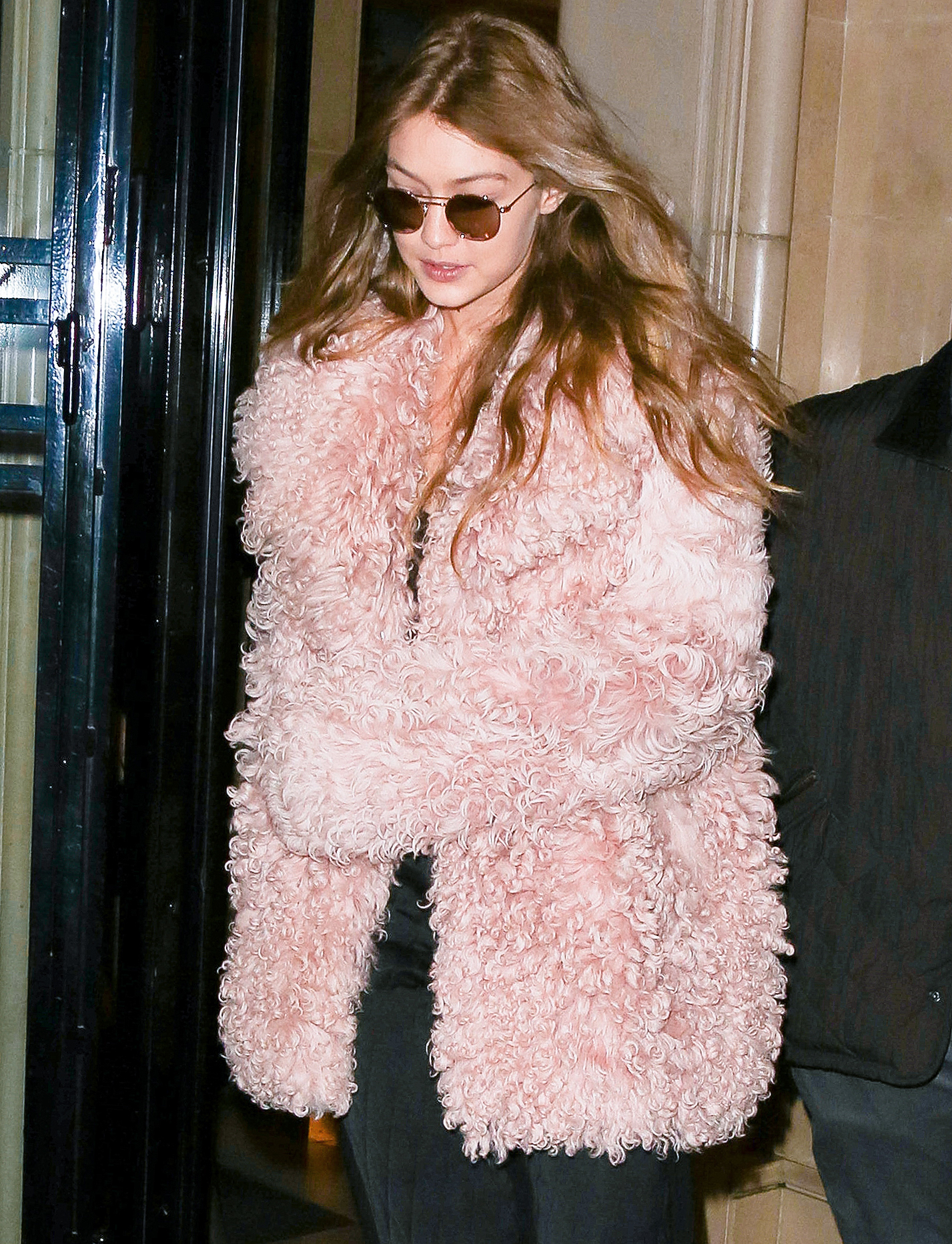 Gigi Hadid exits the George V hotel in pink and black during PFW