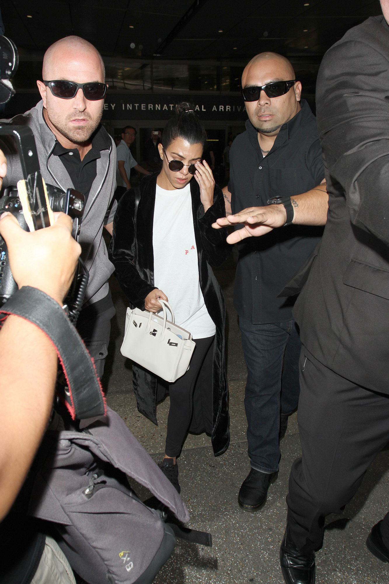 Kourtney Kardashian is flanked by several huge bodyguards as she arrives in Los Angeles on the heels of her sister, Kim reportedly being robbed at gunpoint in Paris. The KUWTK star was seen at LAX with her bodyguards.