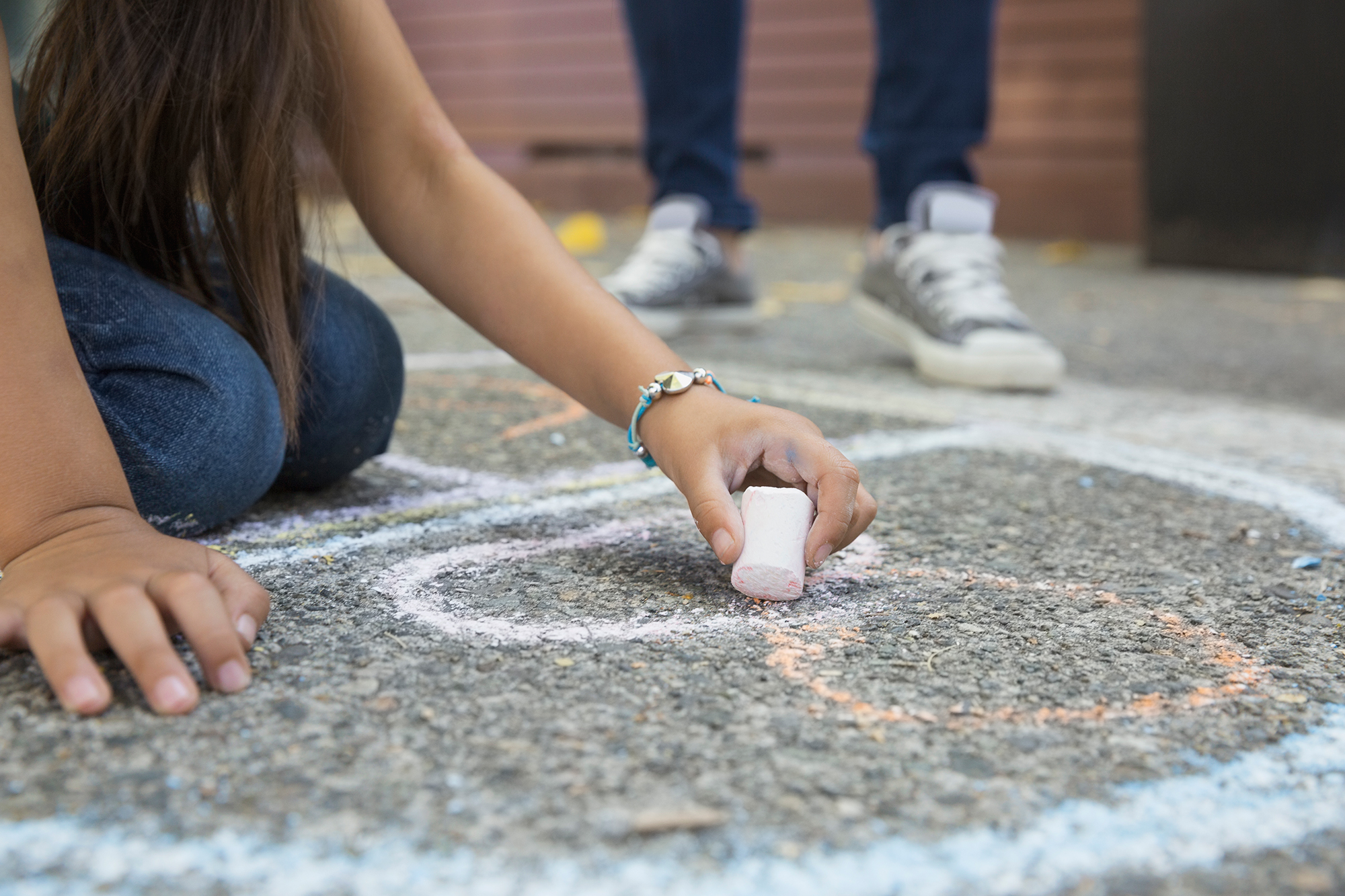 Girl drawing hopscotch number 8 with sidewalk chalk