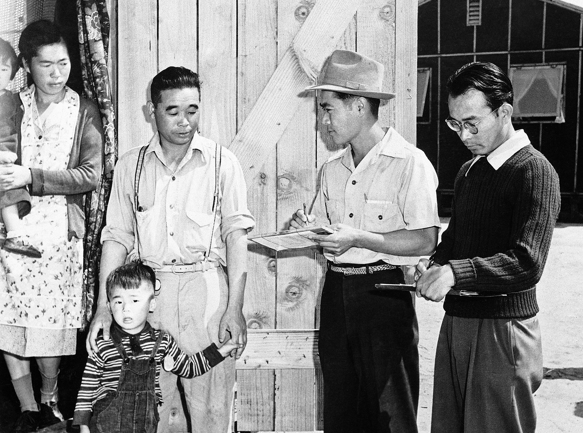 This is a New Japanese family checking in at the big assembly center in Santa Anita, California July 2, 1942, that was established at the race track after the start of the war for West Coast people of Japanese descent. Some 18,500 men, women and children, two thirds of them American citizens, are housed in barracks at the center. They have their own schools under the grandstand in the long room lined with windows, where formerly bets were placed by race track visitors. The internees are fed well and though they live under military rules, their mail censored, and barbed wire surrounding them, various forms of recreation help to make their life more life more. Teams have been formed at the center, diamond fans are rabid. (AP Photo)