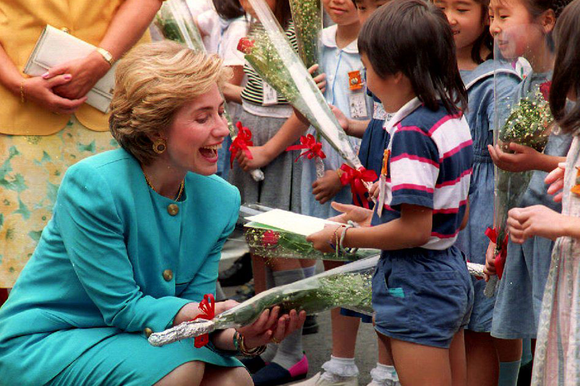 TOKYO, JAPAN - JULY 8: U.S. First Lady Hillary Rodham Clinton laughs as she is presented a bouquet of flowers by Japanee children 08 July 1993 at the Meguro waste incineration plant in Tokyo, Japan. Mrs. Clinton, maintaining a high profile during the G7 summit, is popular in Japan. (Photo credit should read DAVID NELSON/AFP/Getty Images)