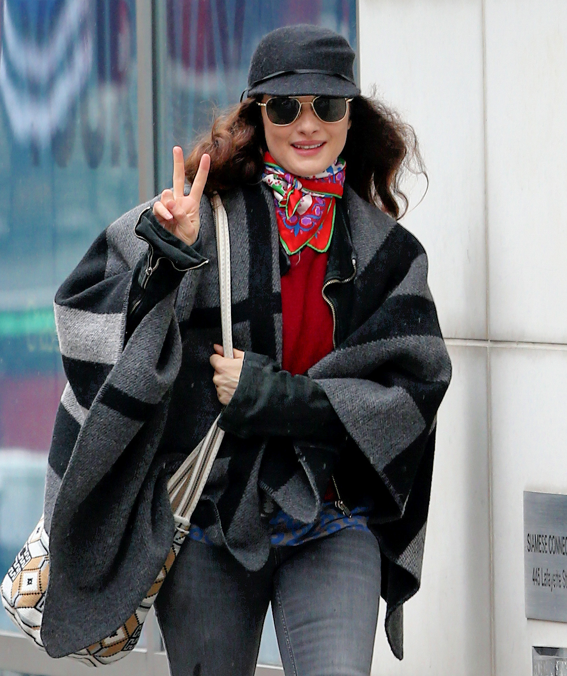Actress Rachel Weisz, wearing a striped shawl, knee-length boots and her favorite stained jeans, flashes the peace sign as she arrives for her matinee performance of 'Plenty' at Public Theater in New York City
