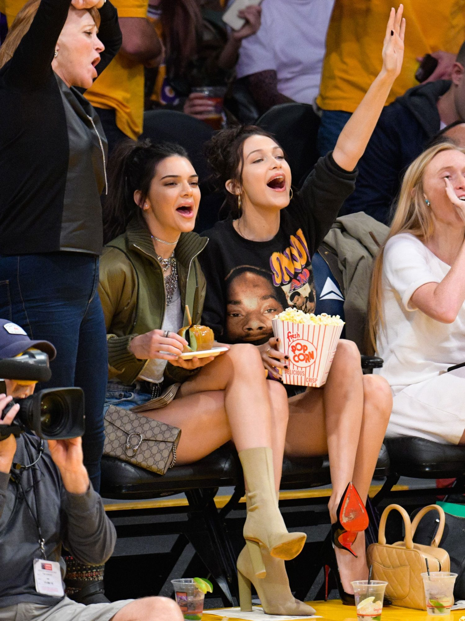 The model friendsknow how to makeeating a caramel apple and bucket of popcorn look chic while cheering on the Los Angeles Lakers at the Staples Center.
