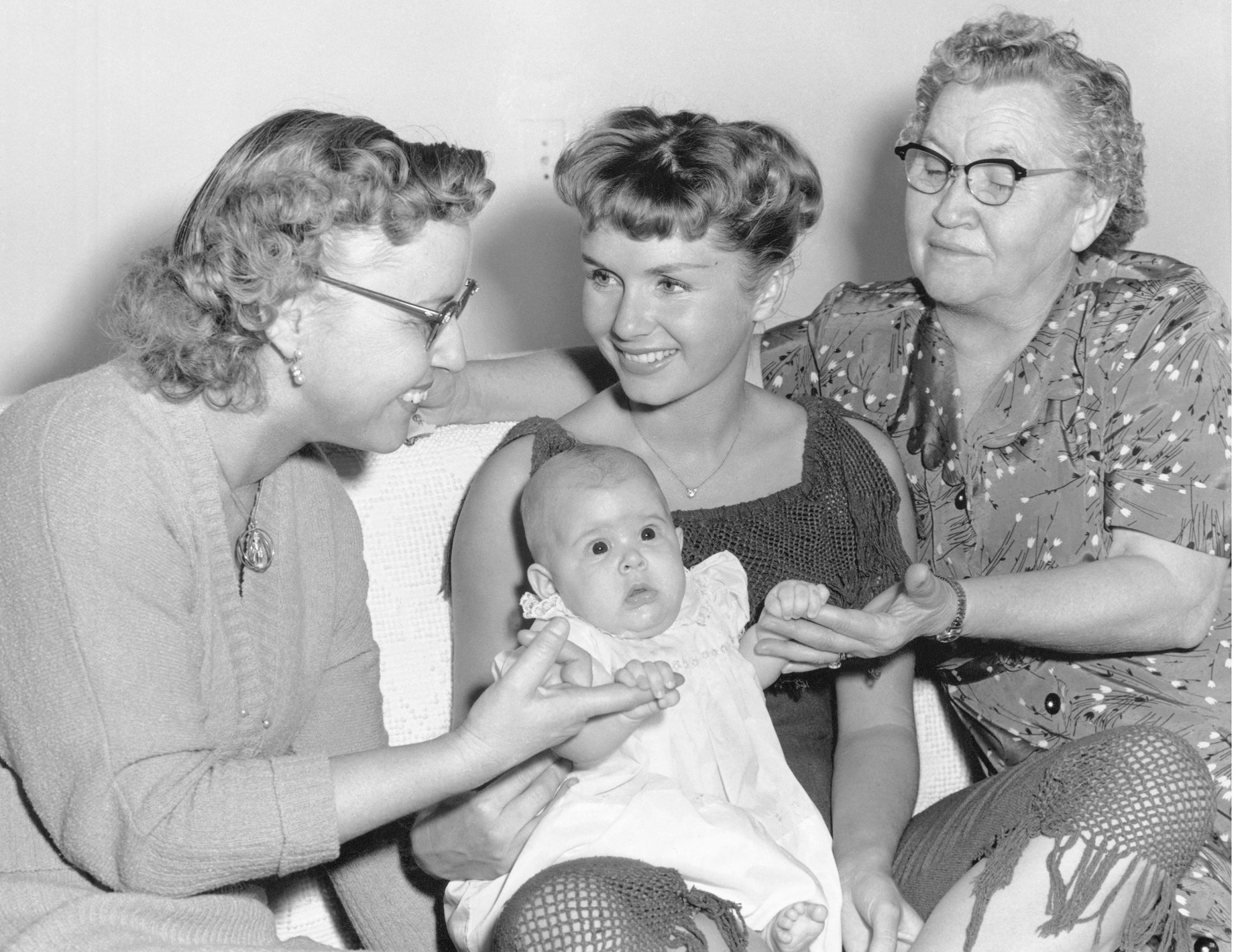 (Original Caption) Trio of Mothers. Hollywood: Actress Debbie Reynolds, holding daughter Carrie Frances Fisher, compares notes with her mother, Mrs. Maxene Reynolds (L) and her mother's mother, Mrs. Maxene Harmon (R). The occasion for the four generation get-together -- Mother's Day, of course.