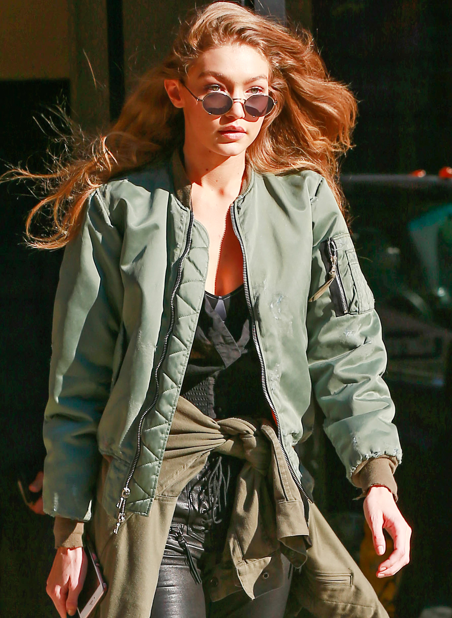 Gigi Hadid wears a green bomber jacket and leather pants in New York City