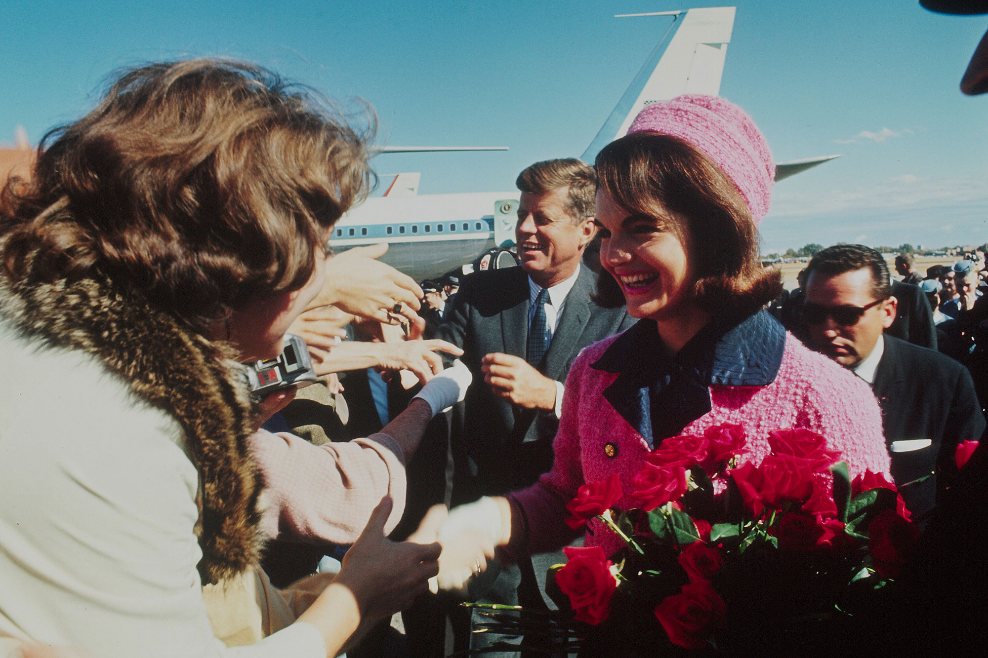 Contributor 1BA3CBCC Pres. John F. Kennedy & bouquet-carrying wife Jacqueline Kennedy shaking hands w. crowd after arriving at Love Field on a fateful campaign tour of city which would result in the President's assassination.