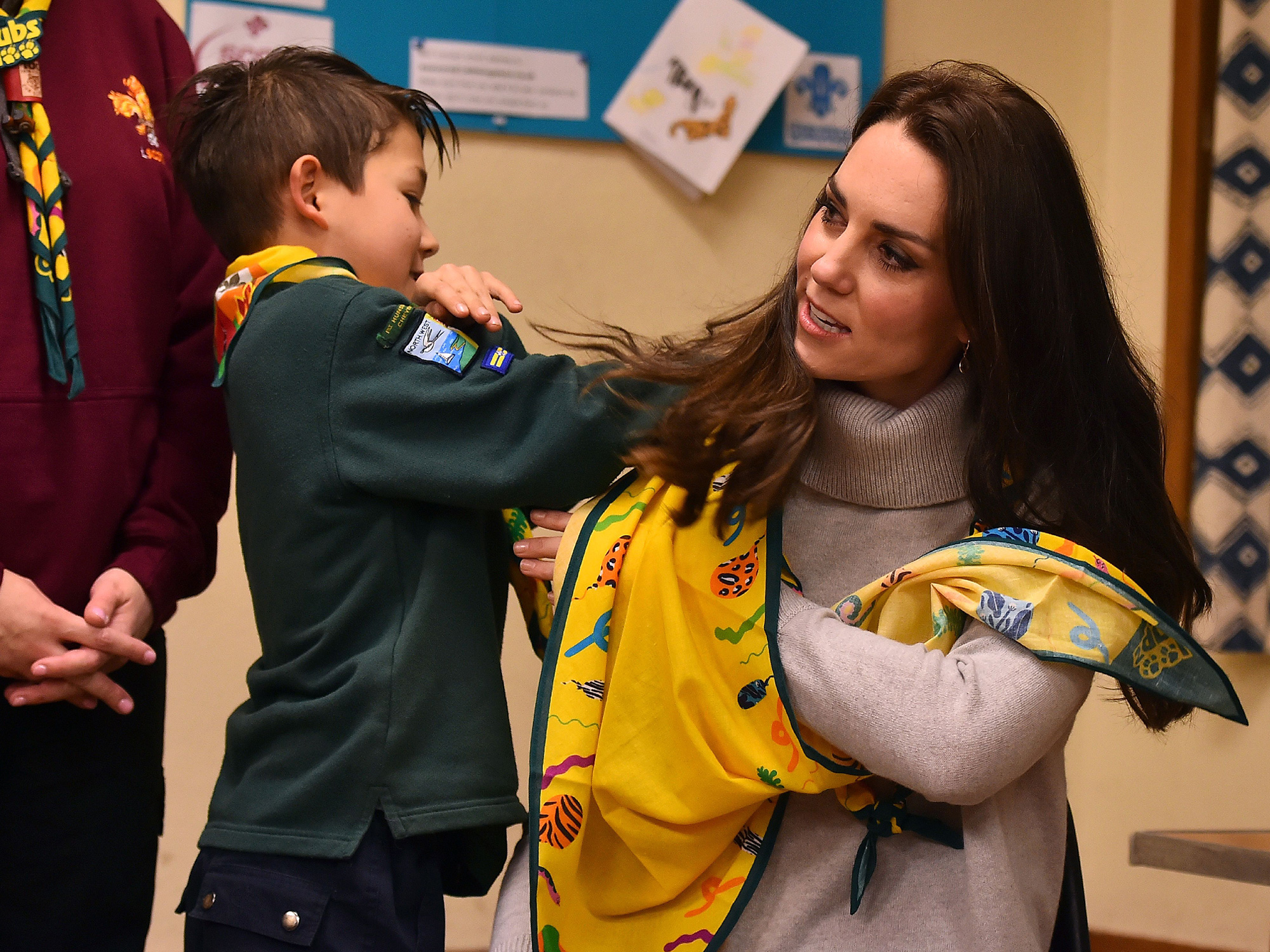 A cub scout uses a neckerchief to show Britain's Catherine, Duchess of Cambridge, how to support a broken arm, during a Cub Scout Pack meeting with cubs from the Kings Lynn District, in Kings Lynn, eastern England, on December 14, 2016, to celebrate 100 years of Cubs. The Duchess attended a special Cub Scout Pack meeting with Cubs from the Kings Lynn District to celebrate 100 years of Cubs. Cub Scouting was co-founded by Robert Baden-Powell and Vera Barclay on the 16th December 1916. / AFP / POOL / BEN STANSALL (Photo credit should read BEN STANSALL/AFP/Getty Images)