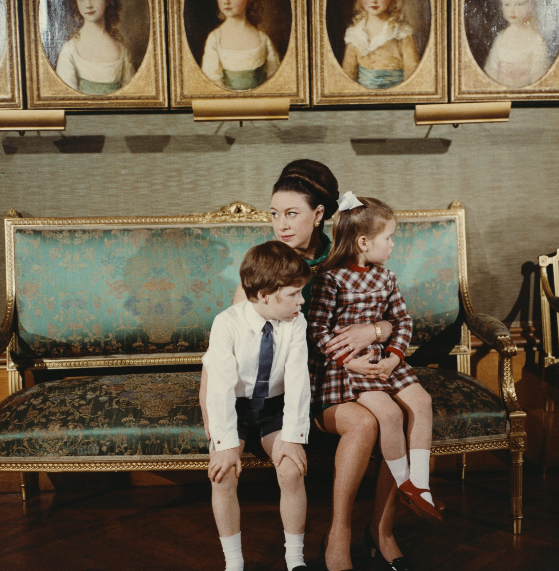 Members of the British Royal Family, Princess Margaret, Countess of Snowdon (1930-2002) pictured holding her children, David Armstrong-Jones, Viscount Linley and Lady Sarah Armstrong-Jones on her knees during filming of the television documentary 'Royal Family' in London in 1969. The documentary would be first broadcast to the nation's television viewers on 21st June 1969. (Photo by Rolls Press/Popperfoto/Getty Images)