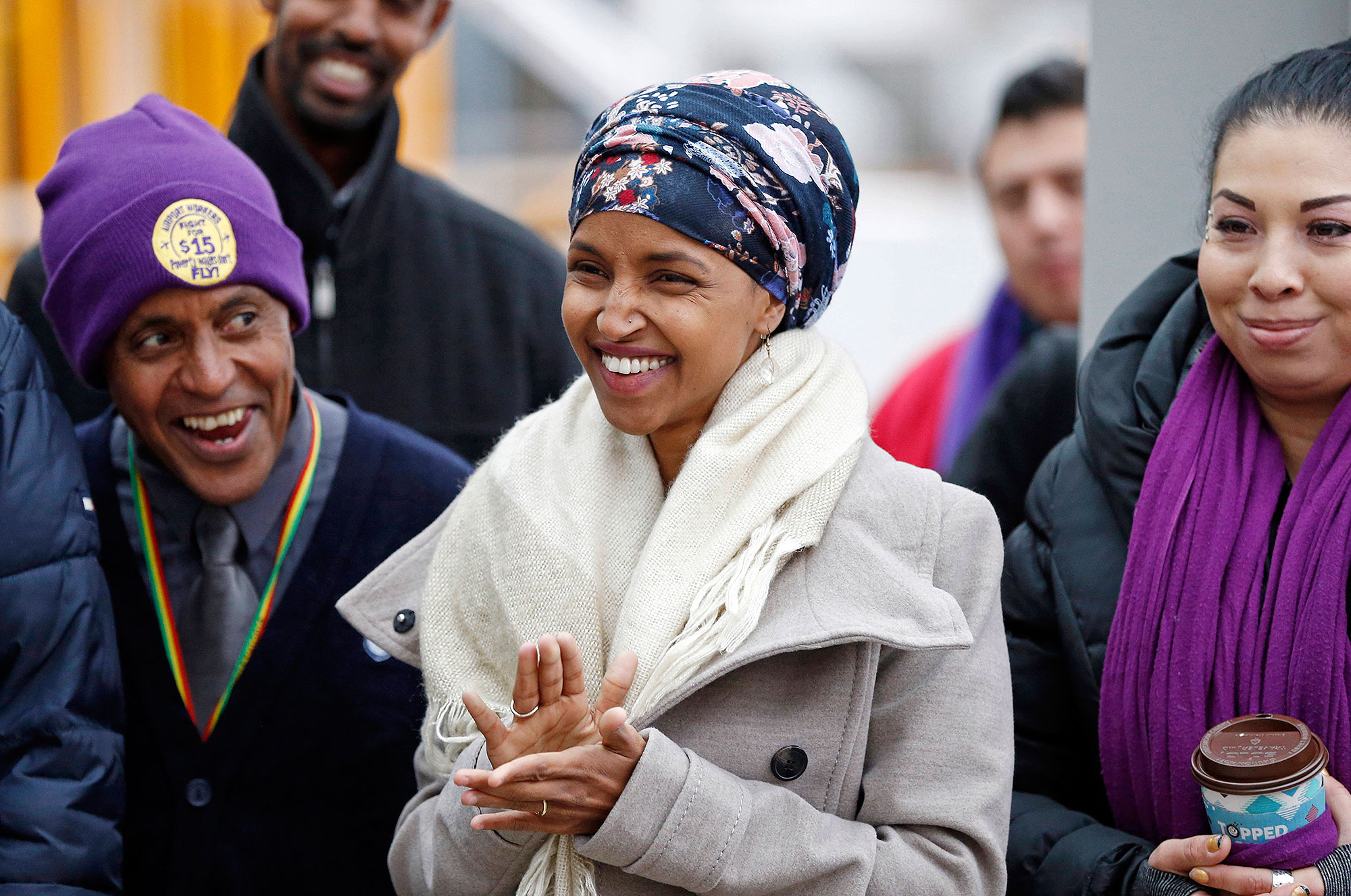 FILE - In this Tuesday, Nov. 29, 2016 file photo, Ilhan Omar, center, applauds during a rally at the Minneapolis-St. Paul International Airport in Minneapolis. Omar, the nation's first elected Somali-American lawmaker says she was harassed by a taxicab driver in Washington, D.C. this week. Minnesota Rep.-elect Omar said the cab driver called her ISIS, lobbed sexist taunts and threatened to remove her hijab during a brief ride on Tuesday Dec. 6, 2016, after a White House meeting on criminal justice reform. (AP Photo/Jim Mone, File)