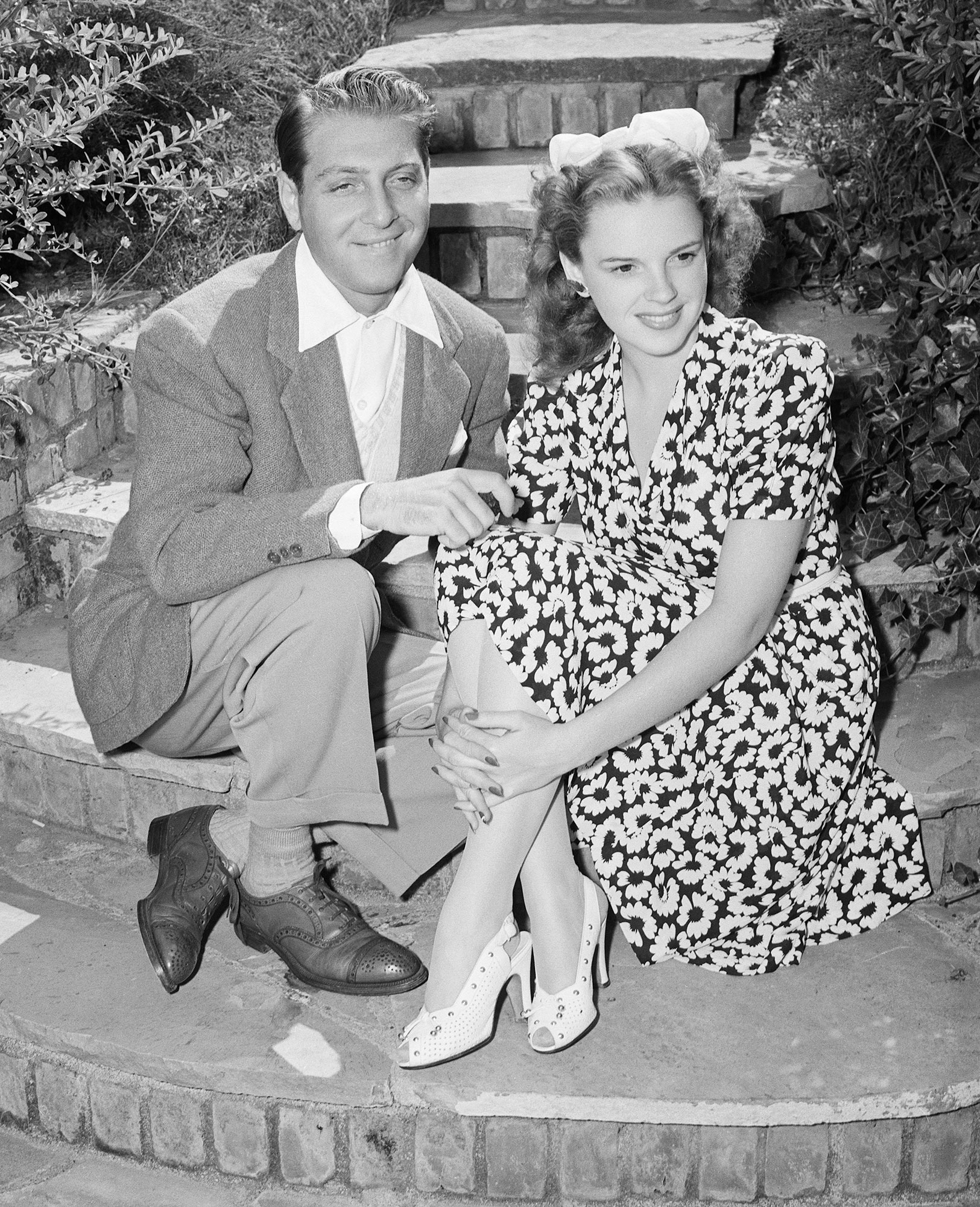 (Original Caption) 6/1941-Hollywood, CA- Judy Garland, singing star, and her fiance, composer-arranger David Rose, relax for a moment, as they make their first appearance together since announcing their engagement. The couple plan to be married some time next year.